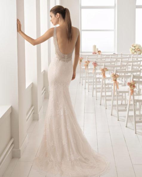 Vestido de novia estilo romántico en encaje y pedreria con escote barco. Espalda con efecto tattoo y pedreria frost. en color nude.