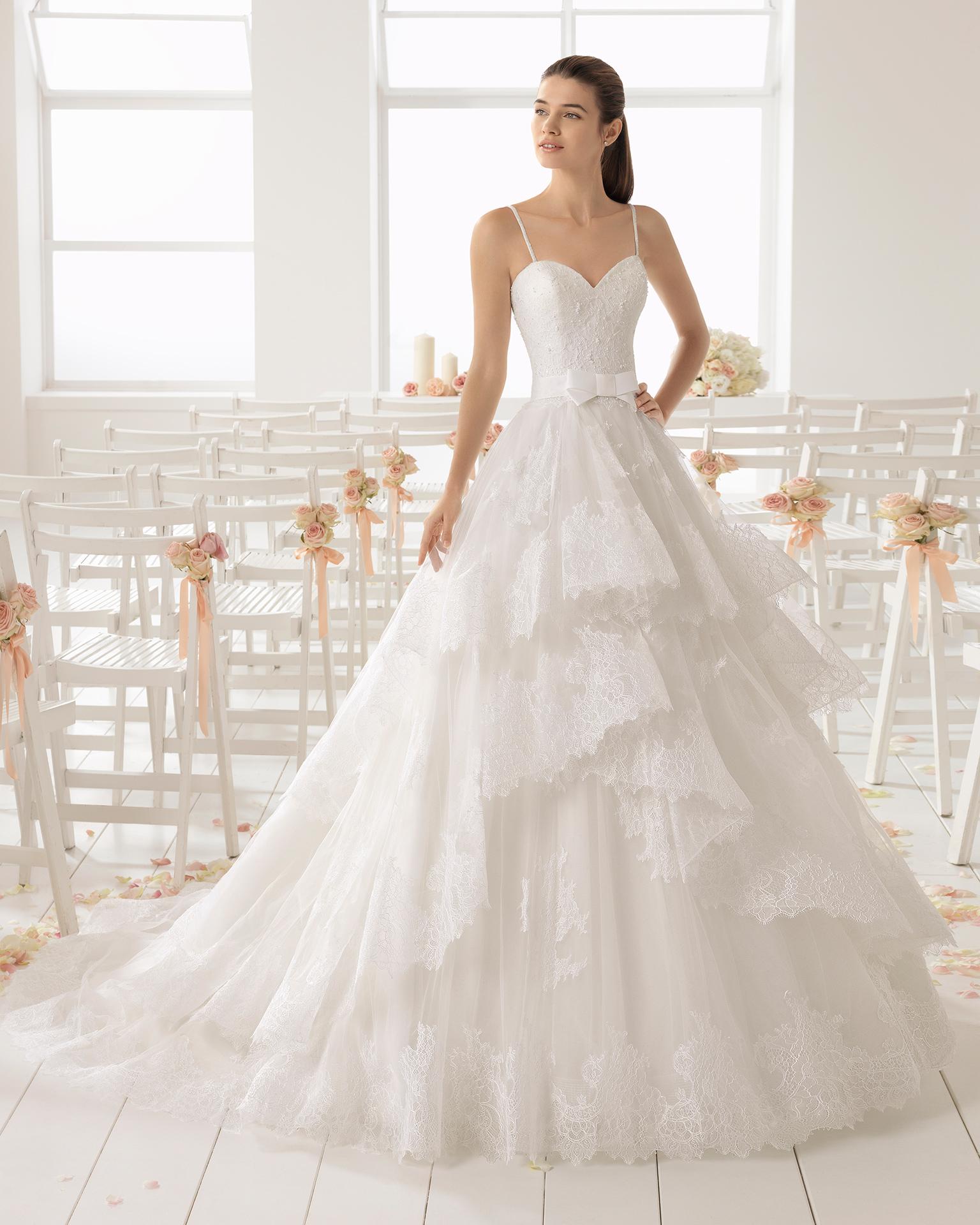 فستان زفاف ذو شكل هرمي من الدانتيل المزيّن بالخرز مع تقويرة رومنسية وفتحة ظهر كبيرة وتنورة فضفاضة.