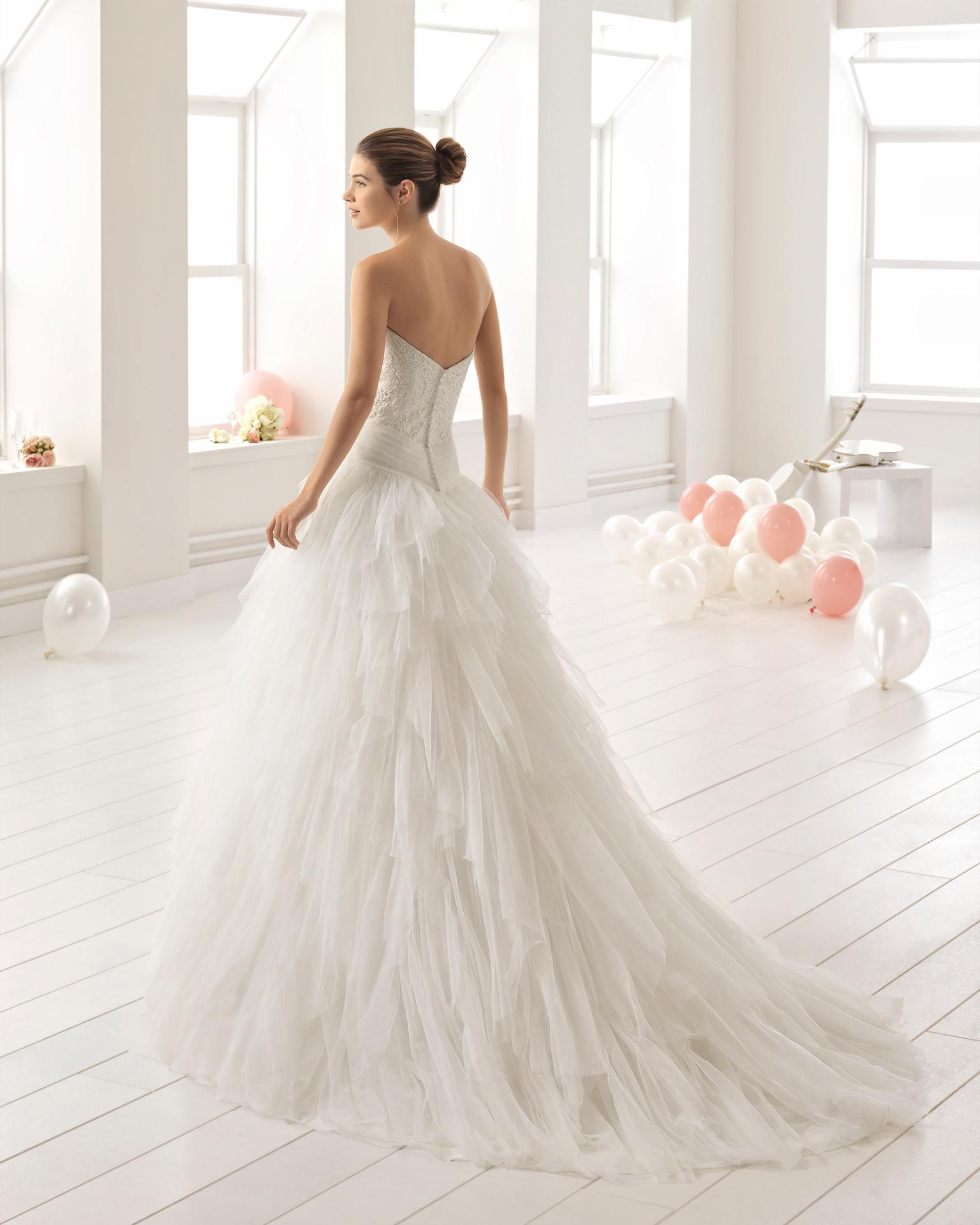Vestido de novia estilo línea A en encaje y pedreria con escote corazón con falda de volantes.