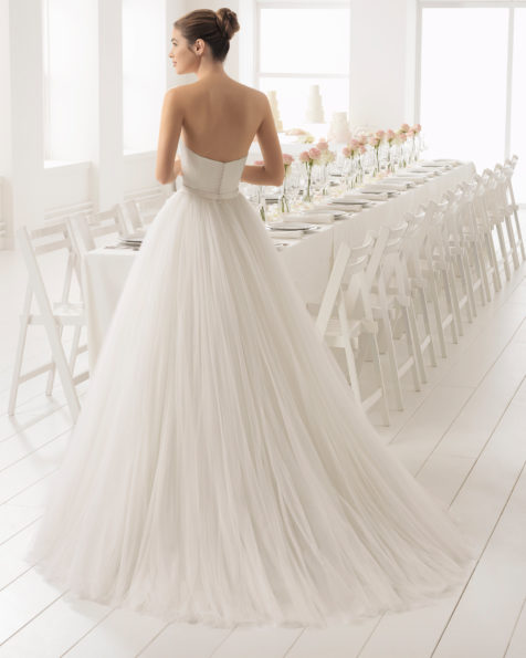 A-line tulle and duchess satin strapless wedding dress with bow at waist.