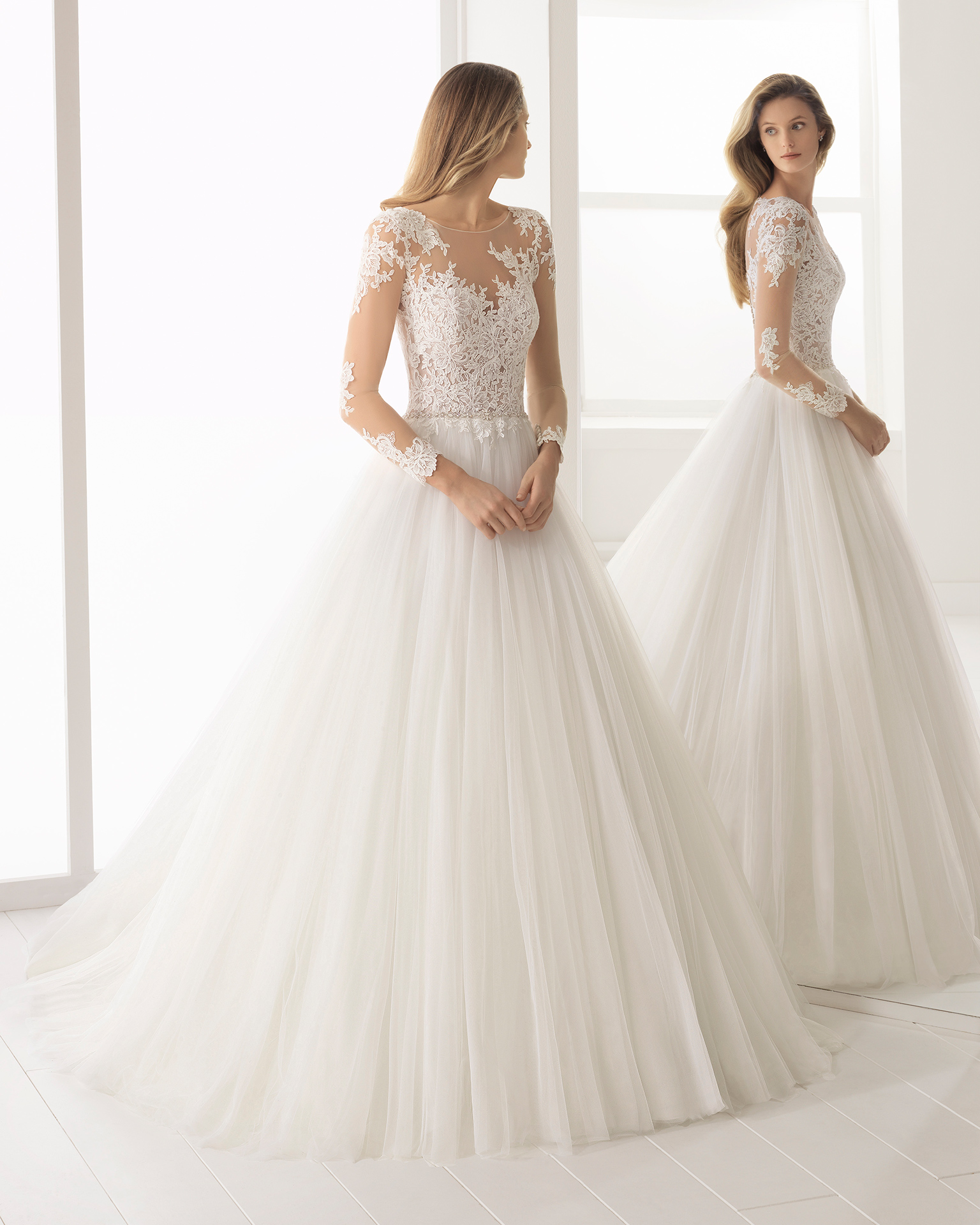 A-line beaded sheer lace and tulle wedding dress with long sleeves and full skirt.