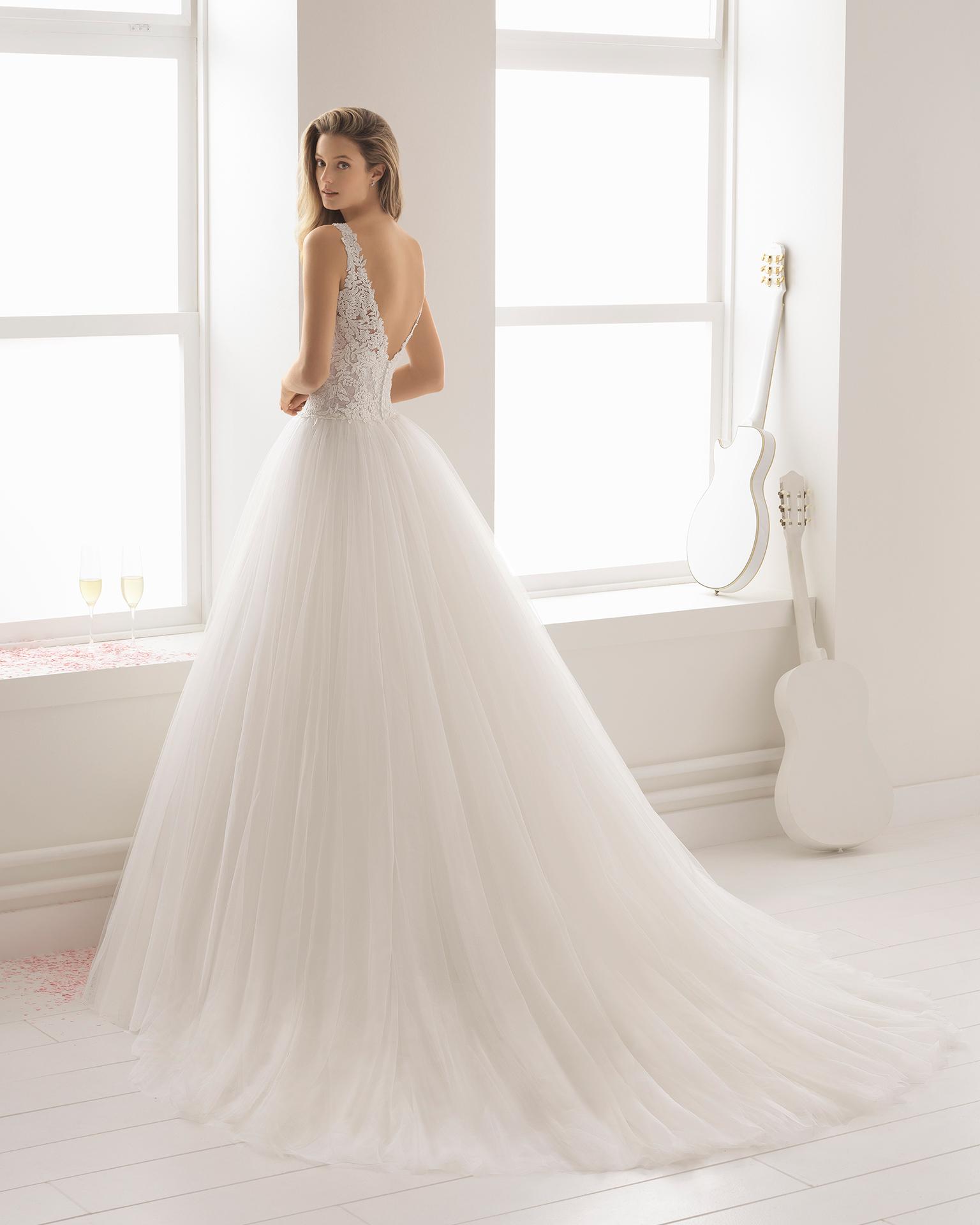 Robe de mariée style trapèze en tulle, dentelle transparente et pierreries, col en V, de couleur naturelle et rose pâle.