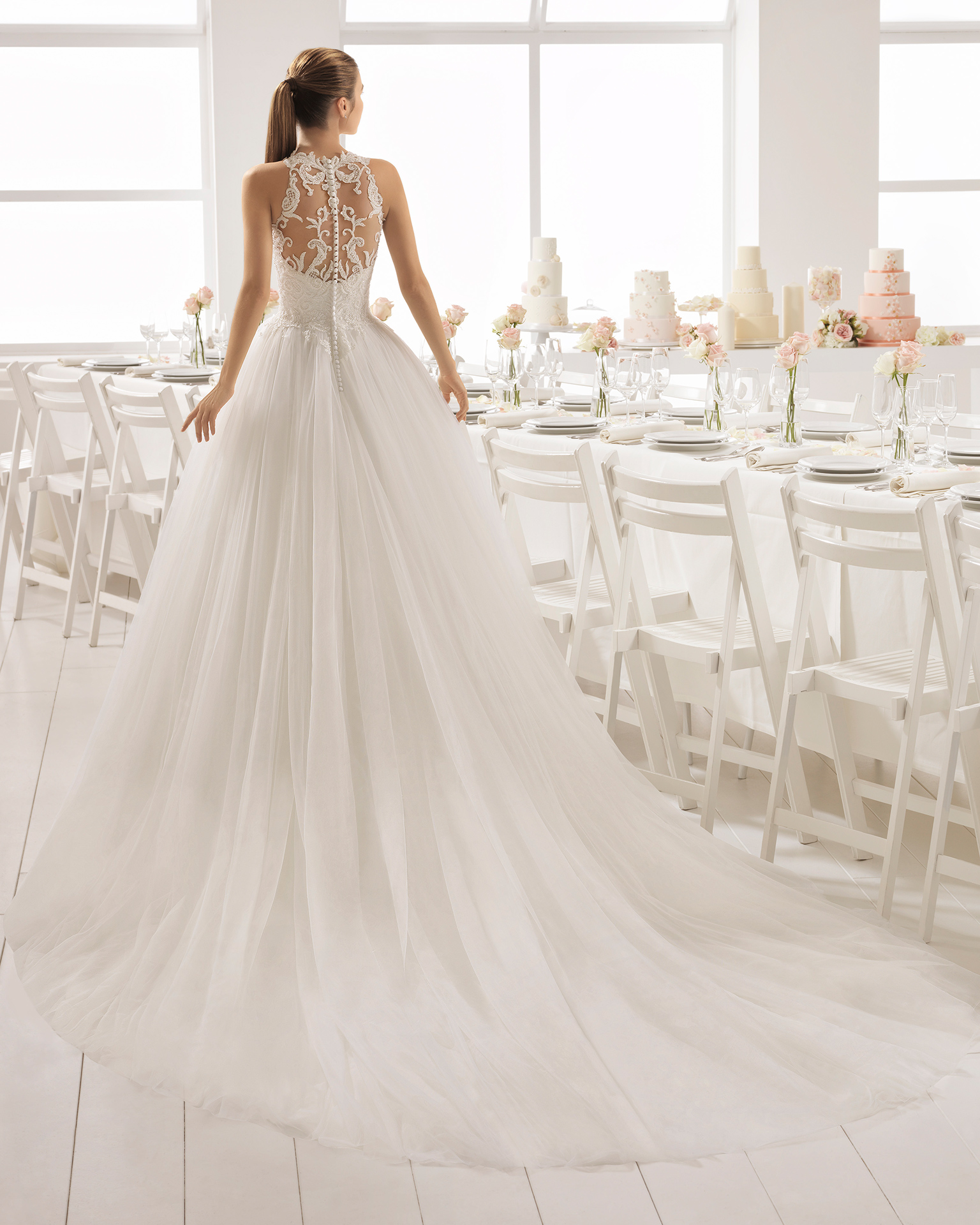 Robe de mariée style romantique en tulle, dentelle et pierreries, avec col halter et jupe créant du volume.