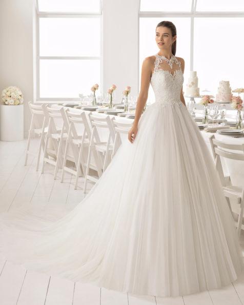 Vestido de noiva estilo romântico de tule, renda e brilhantes, com decote haltere e saia volumosa.