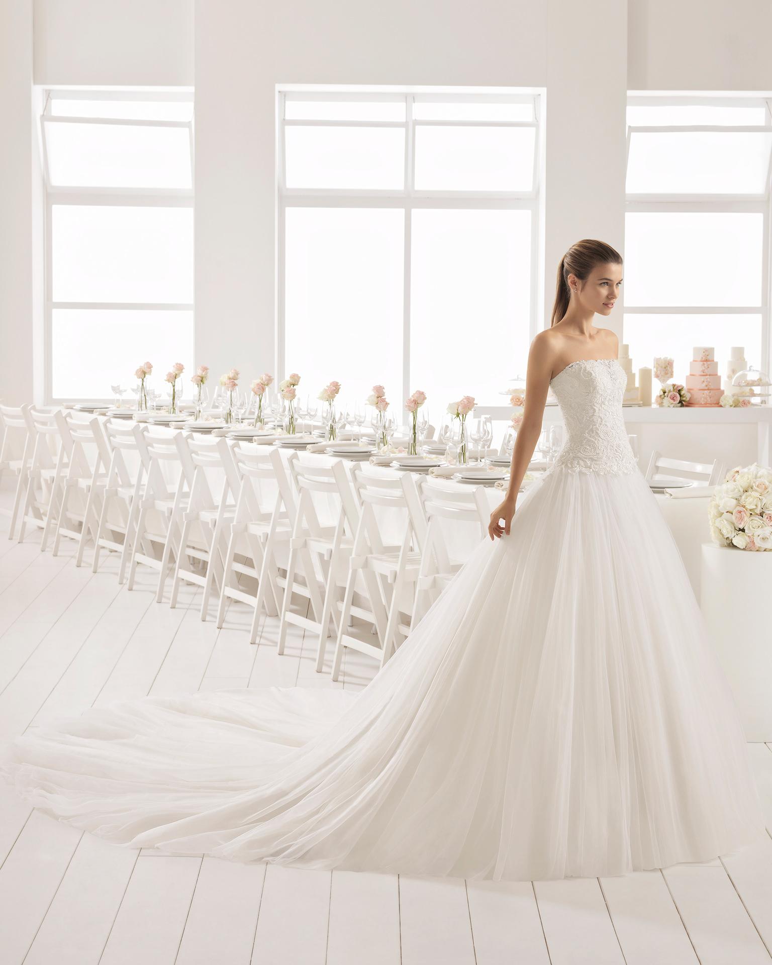 Rochie de mireasă în stil romantic din tul, dantelă și strasuri, cu decolteu fără bretele cu fustă cu volum.