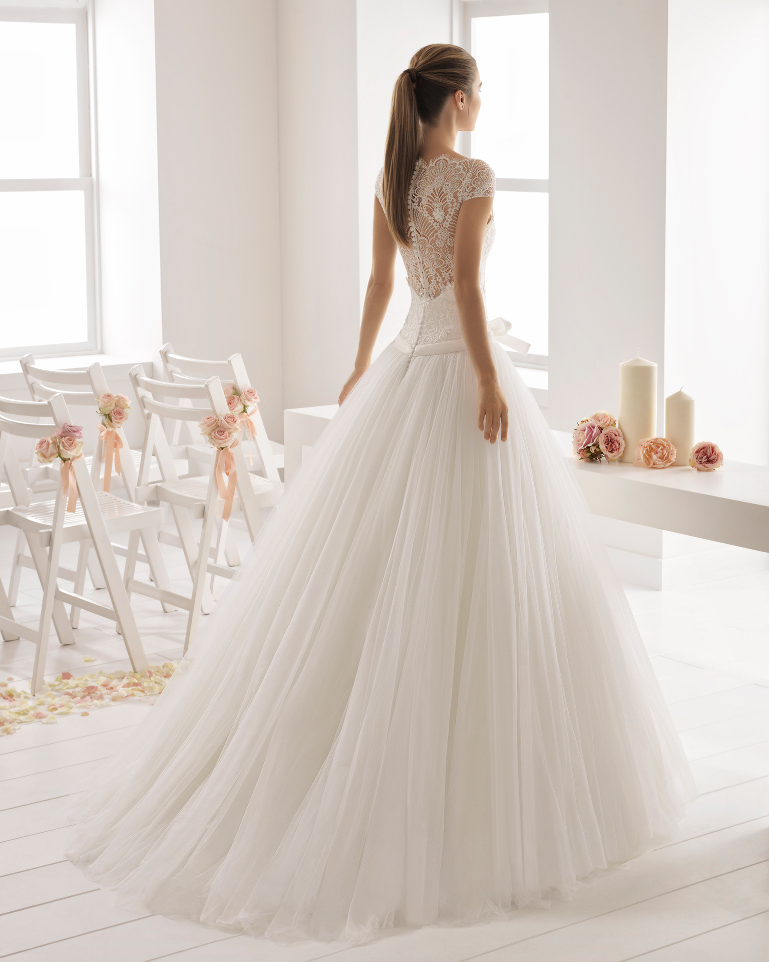 Romantisches Brautkleid aus Tüll und Spitze mit Strassbesatz, Illusionsausschnitt, Rücken aus Spitze und Strass, Schleife an der Taille.