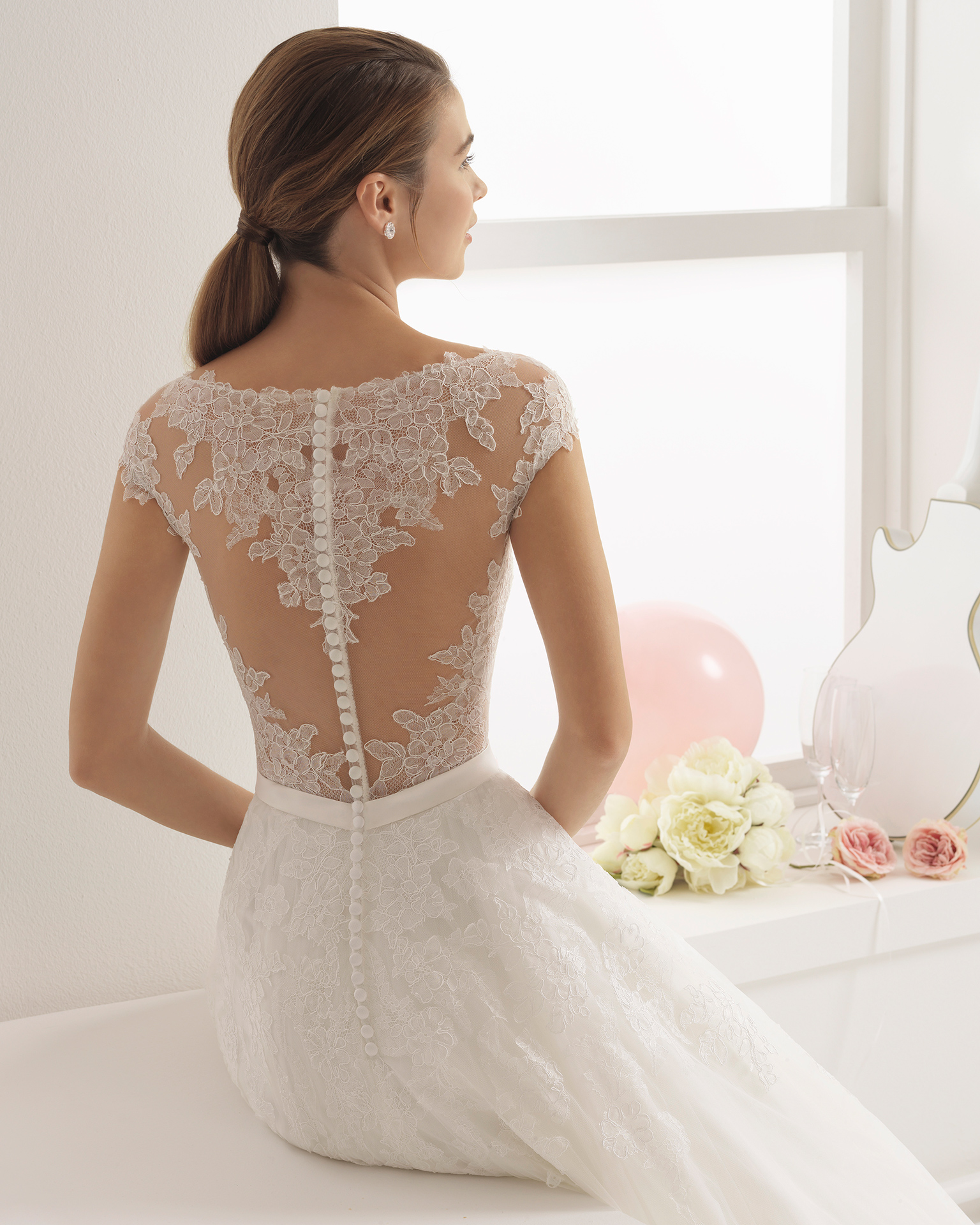 Romantic-style lace wedding dress with illusion neckline and lace back with lace appliqués.