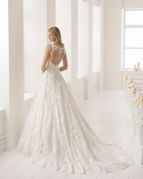 فستان زفاف ذو تصميم رومنسي من الدانتيل، مع تقويرة رومنسية وفتحة ظهر كبيرة، باللون العاجي.