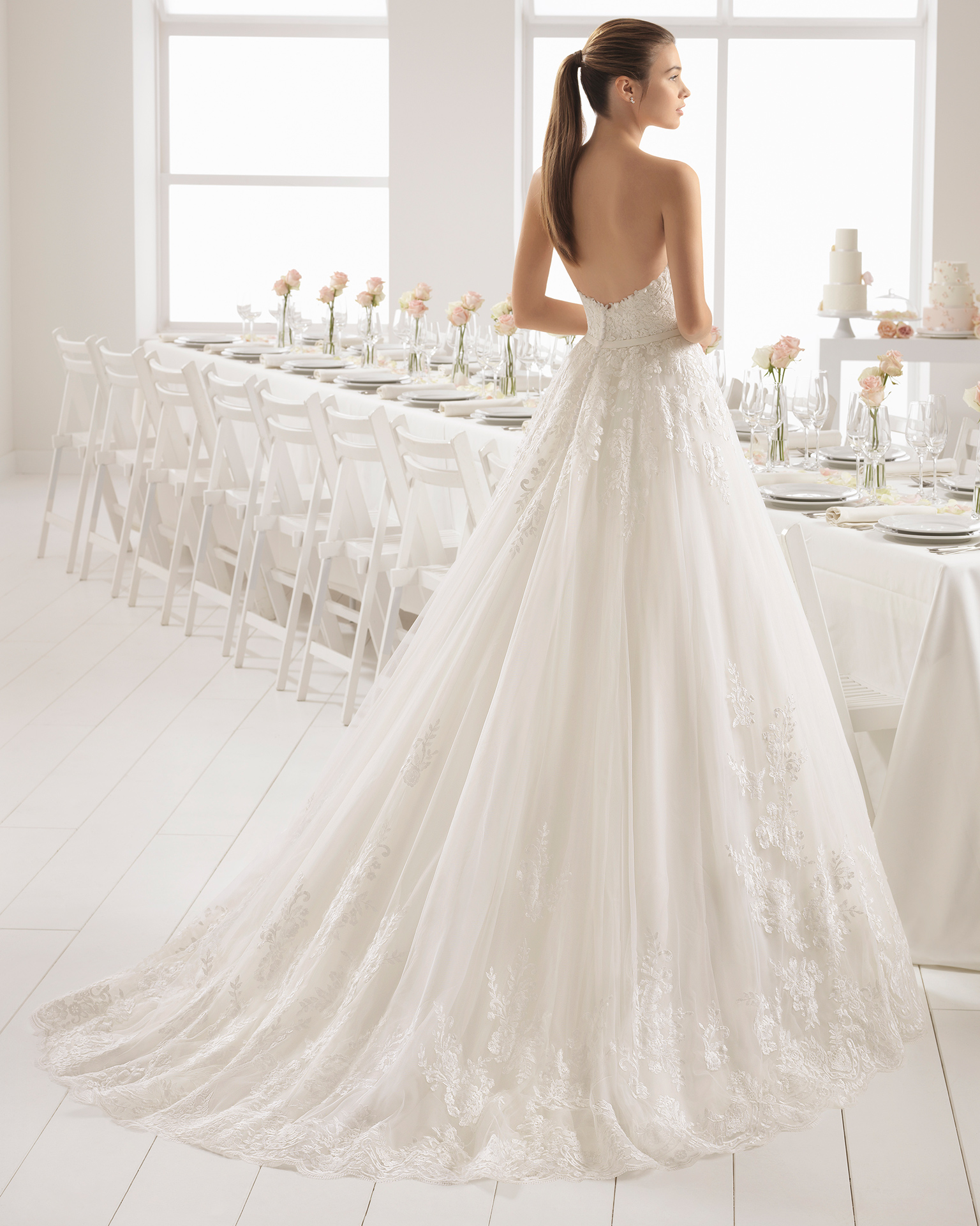 Romantic-style lace wedding dress with sweetheart neckline and bow at waist.