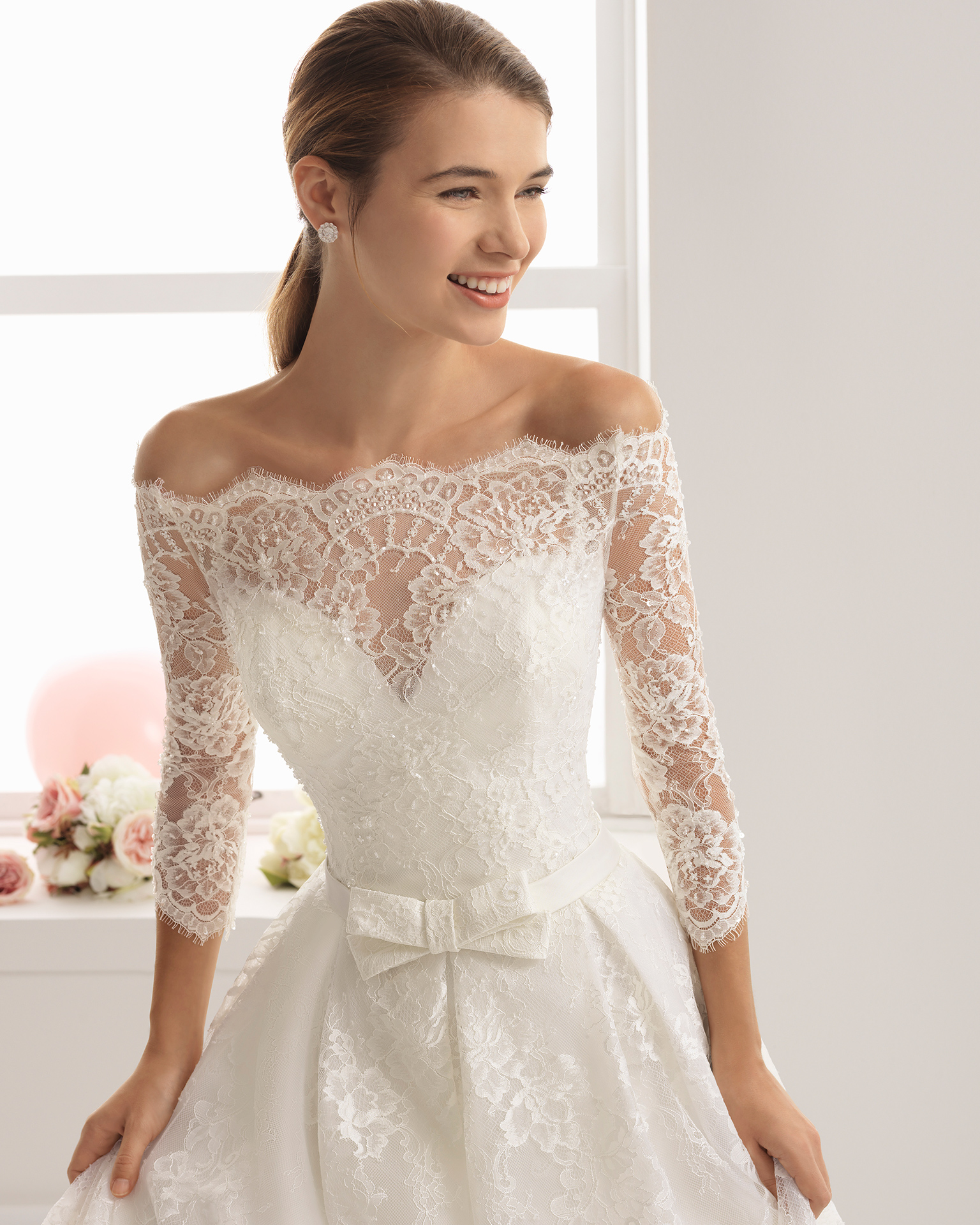 Romantic-style beaded lace wedding dress with three-quarter sleeves and bateau neckline, in ivory, and in rose with bow at waist.