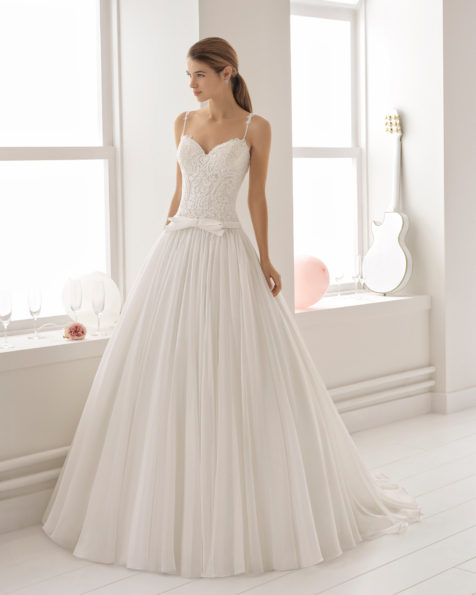 Vestido de novia estilo romántico en voile, encaje y pedreria, con escote corazón y espalda con efecto tattoo con encaje con lazo en la cintura.