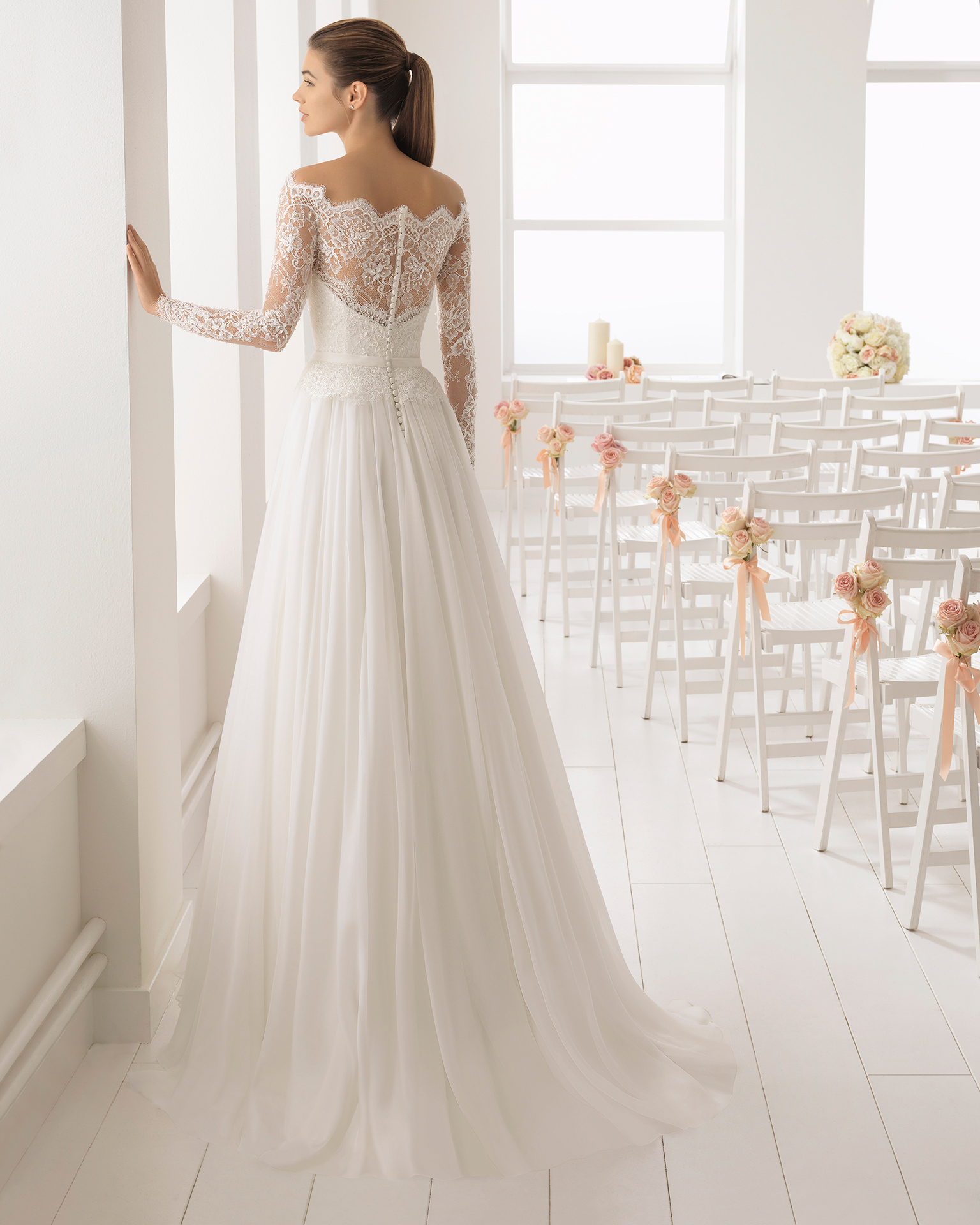 Romantic-style beaded lace and voile wedding dress with long sleeves and off-the-shoulder neckline.