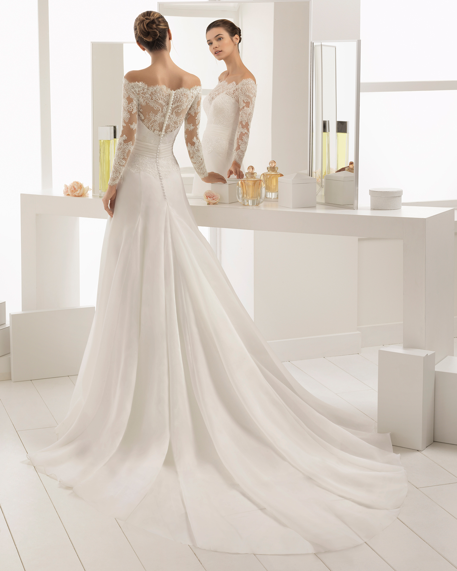 Romantic-style beaded lace and organza wedding dress with long sleeves and off-the-shoulder neckline.