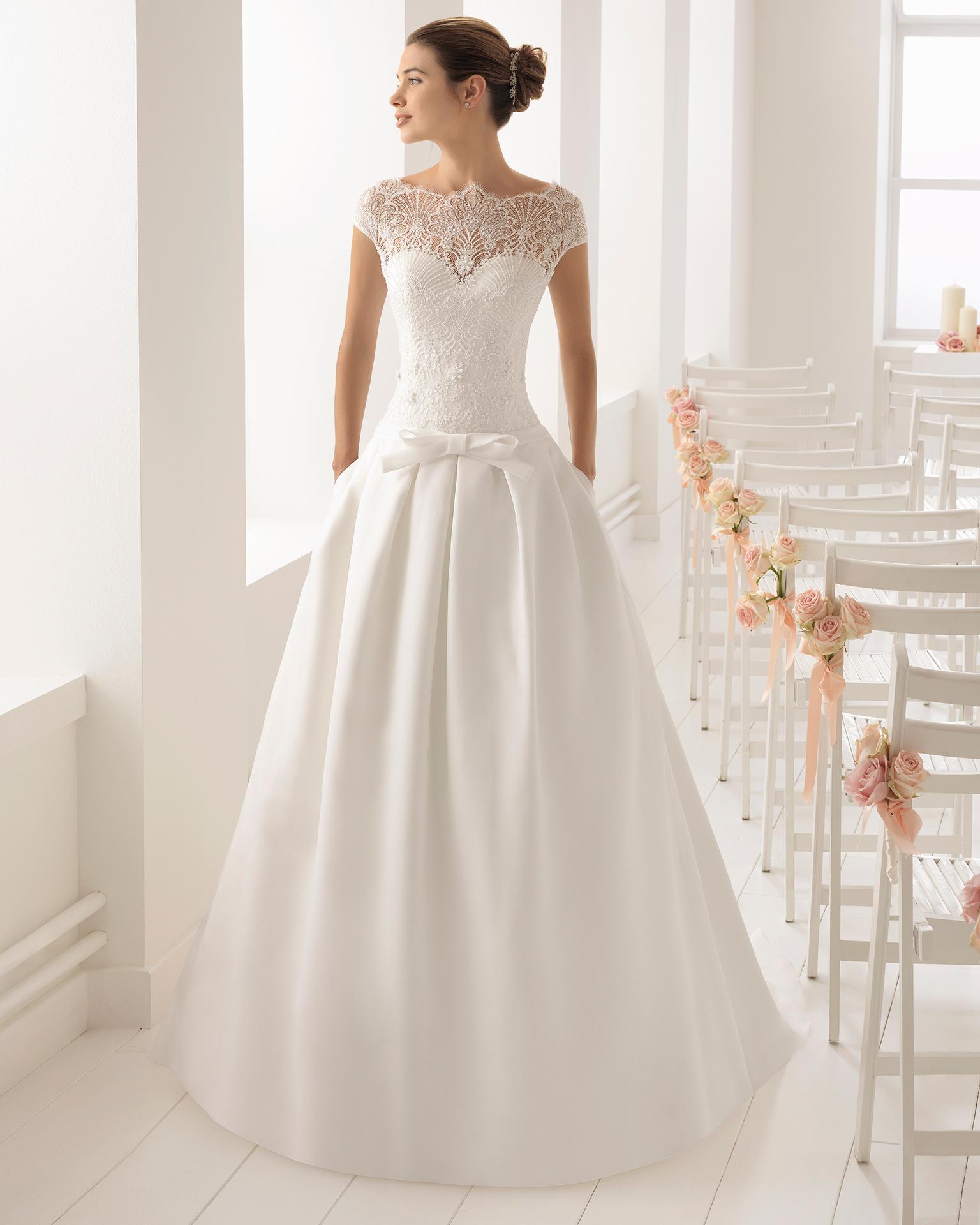 Robe de mariée style romantique en organdi, dentelle et pierreries, avec col illusion et nœud à la taille.