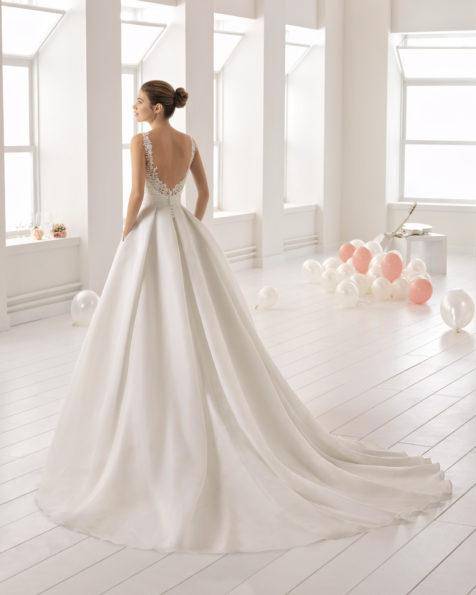Rochie de mireasă în stil romantic din gazar, dantelă și strasuri, cu decolteu în V și spatele decoltat cu buzunare.