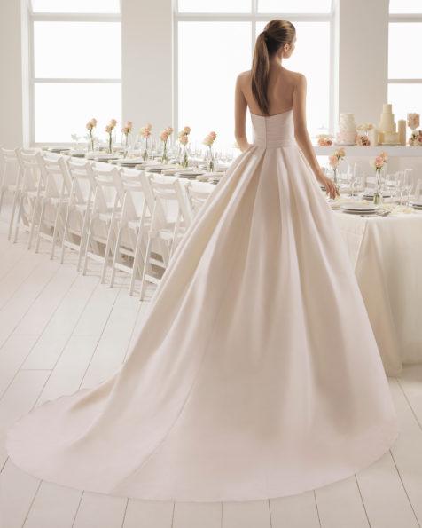 فستان زفاف ذو تصميم رومنسي من الغازار، دون حمّالات للكتف، باللون الوردي، وباللون الطبيعي مع تقويسة على الخصر.