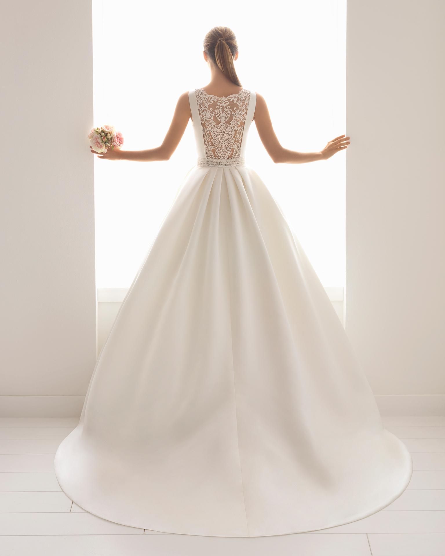 Rochie de mireasă în stil clasic din satin, dantelă și strasuri, cu decolteu tip bărcuță cu buzunare.