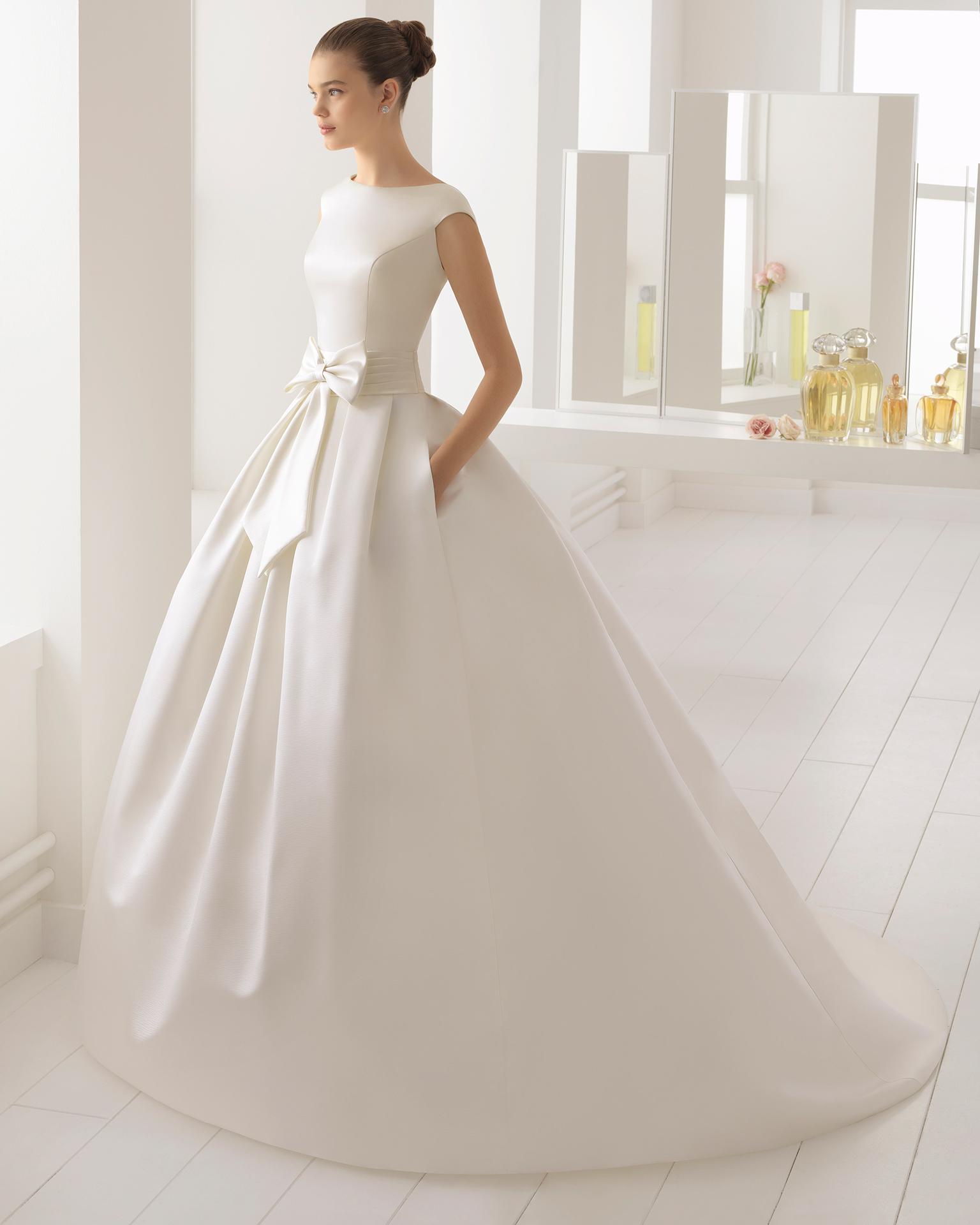 Vestido de novia estilo clásico en raso duquesa, encaje y pedreria, y escote barco en color marfil con lazo en la cintura.