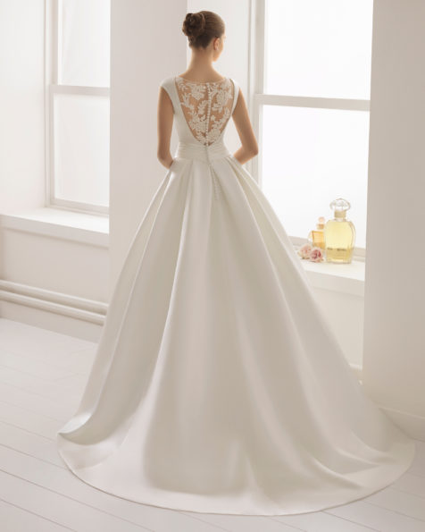 Classic-style beaded lace and duchess satin wedding dress with bateau neckline and bow at waist, in ivory.