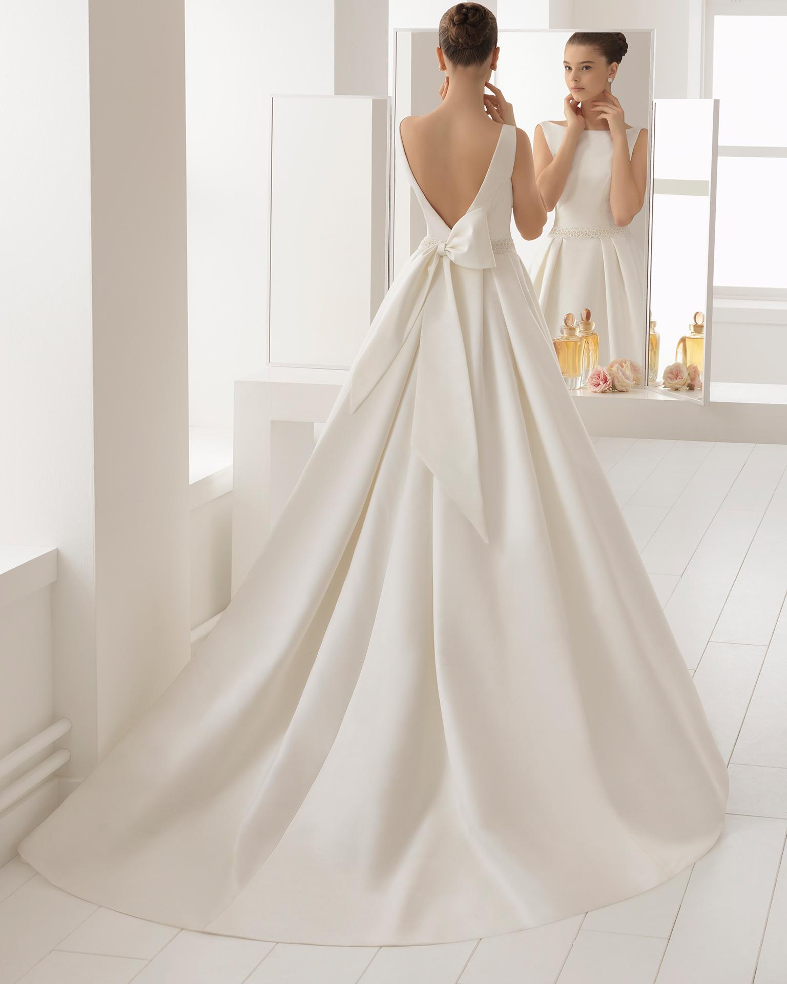 Vestido de novia estilo clásico en otoman y pedreria con escote barco.