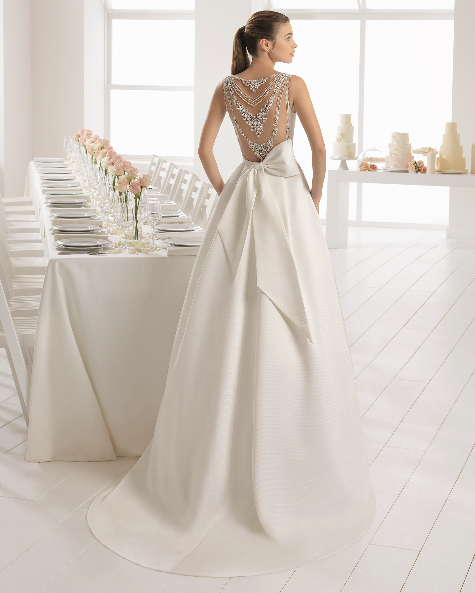 Classic-style ottoman wedding dress with bateau neckline and jeweled back.