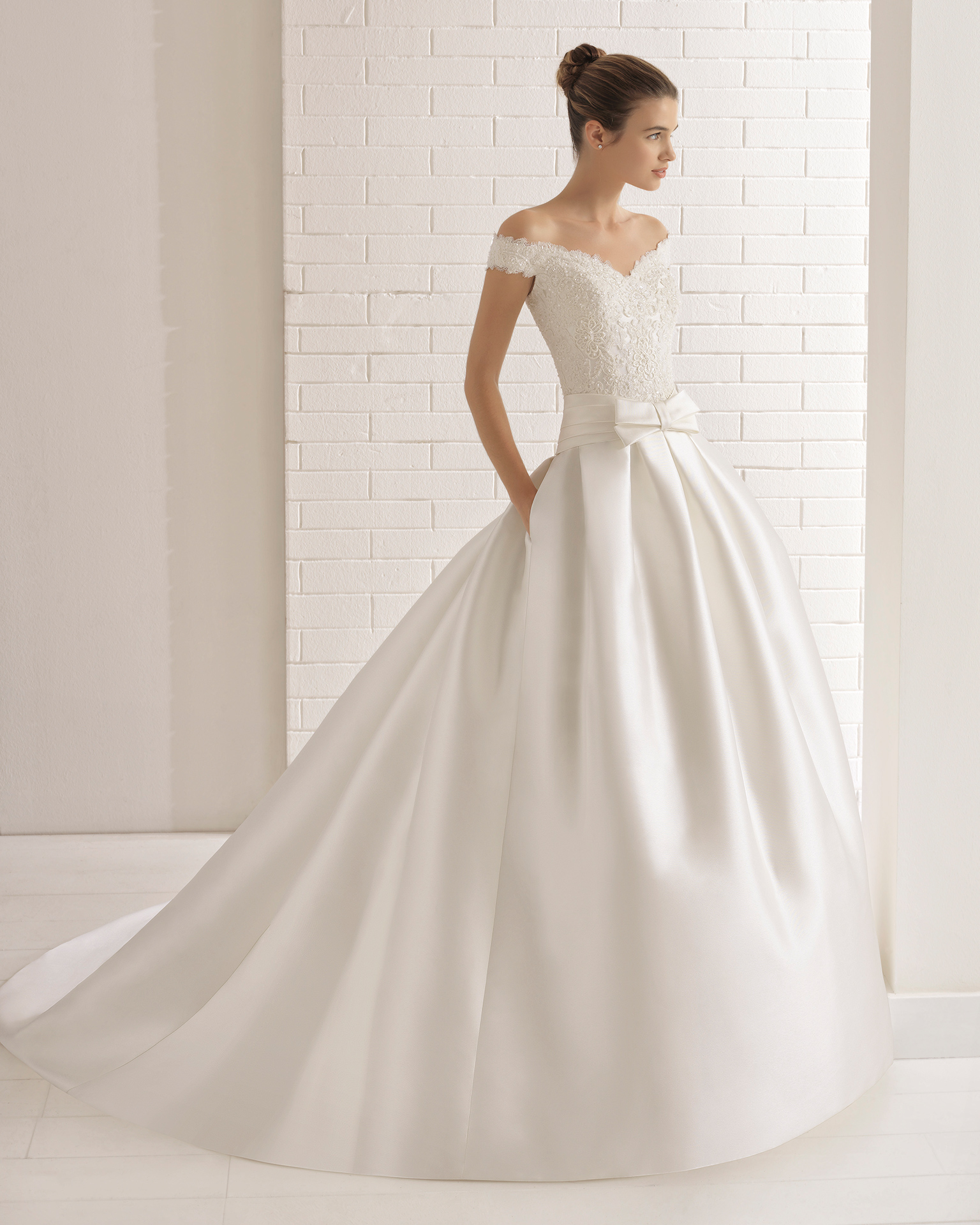 A-line beaded lace and mikado wedding dress with off-the-shoulder neckline, pockets and bow at waist.