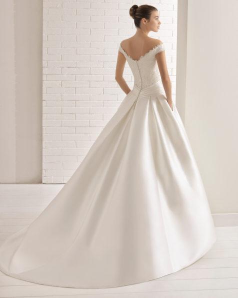 Robe de mariée style trapèze en mikado, dentelle et pierreries, encolure Bardot, nœud à la taille, poches.