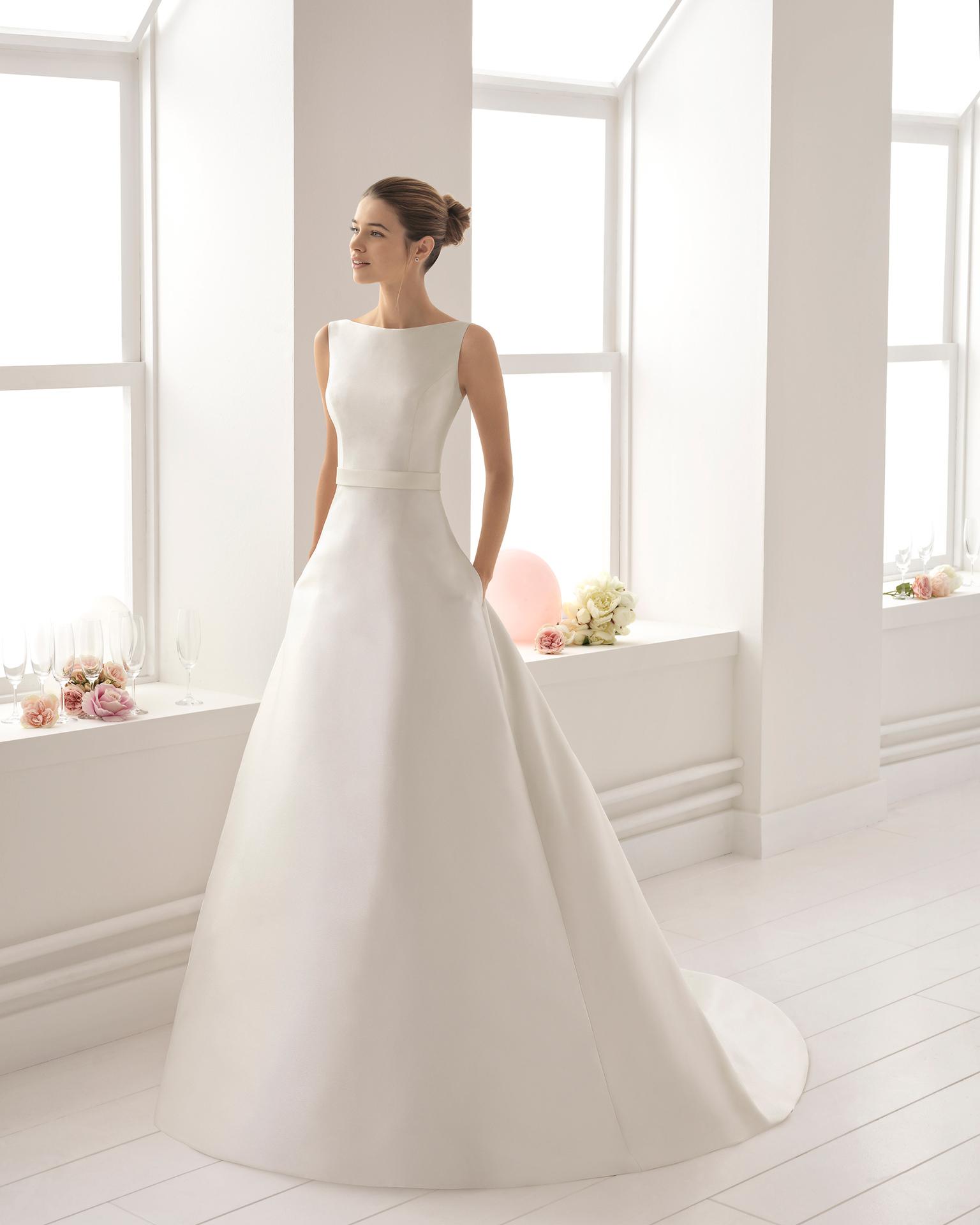Vestido de novia estilo clásico en mikado con escote barco con espalda de encaje y pedreria con lazo trasero en color marfil.