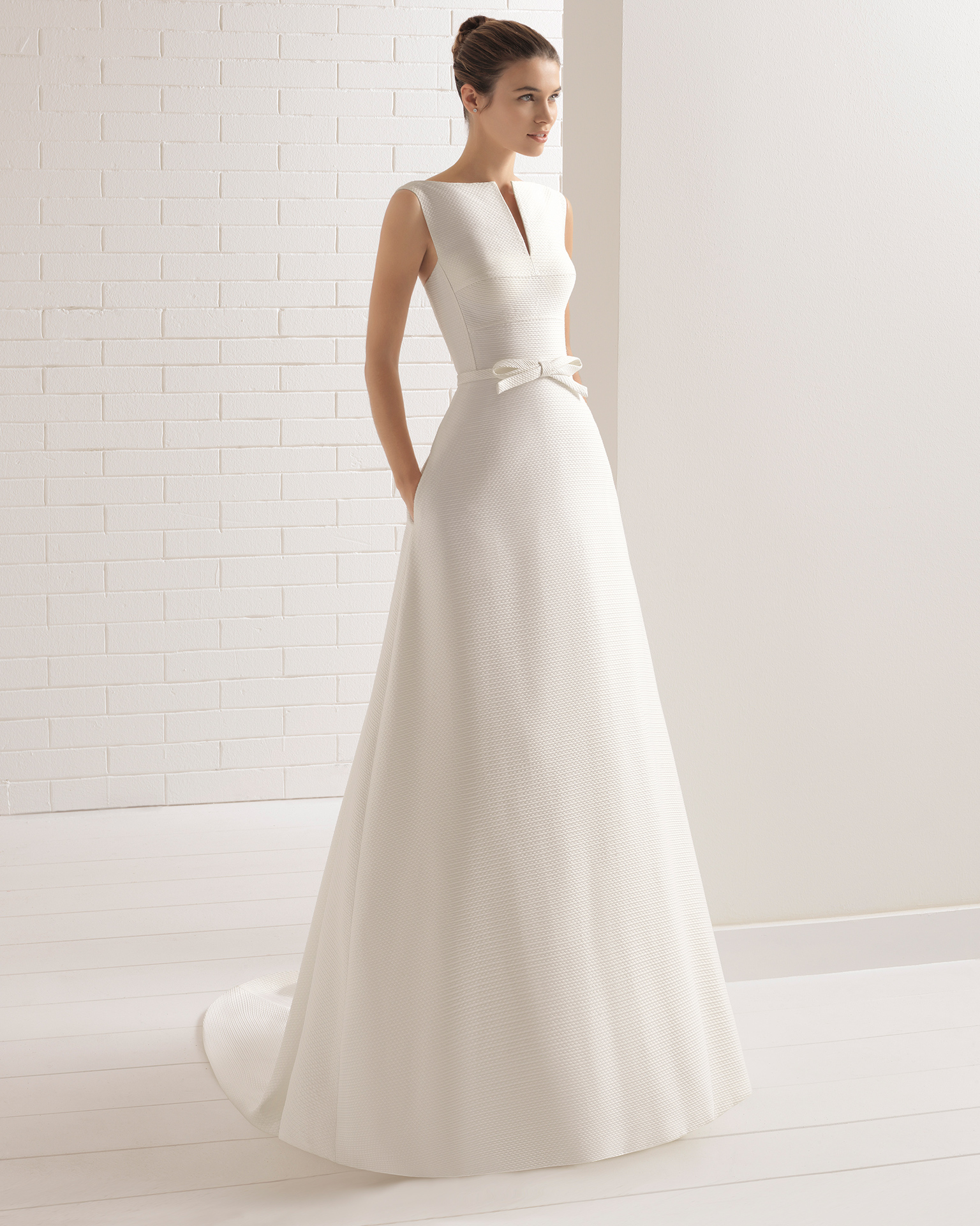 Classic-style capri wedding dress with bateau neckline, front opening and beadwork detail.