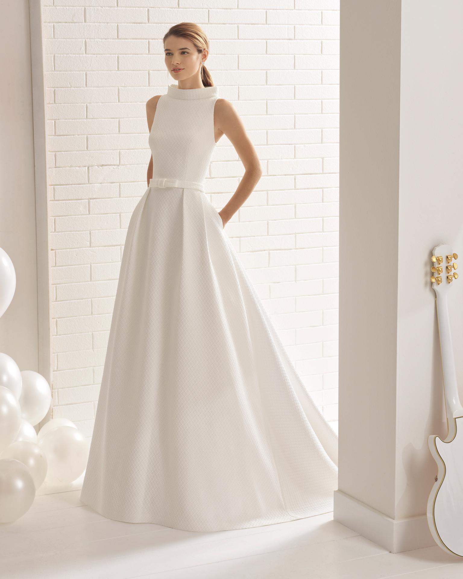 Robe de mariée style classique en cloqué, col bateau avec nœud à la taille et poches.