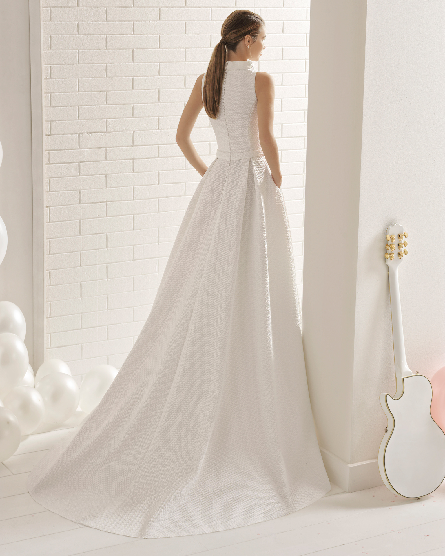 Classic-style cloqué wedding dress with bateau neckline, pockets and bow at waist.