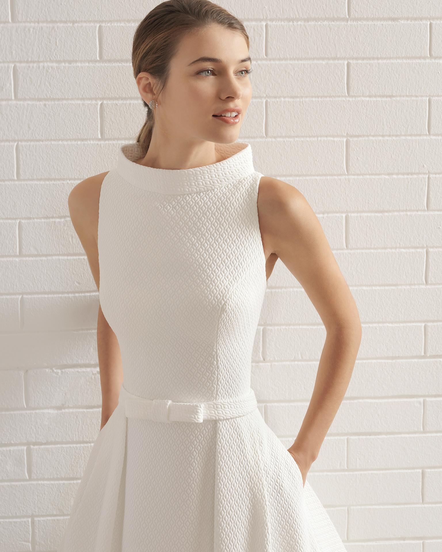 Vestido de novia estilo clásico en cloqué con escote barco con lazo en la cintura y bolsillos.