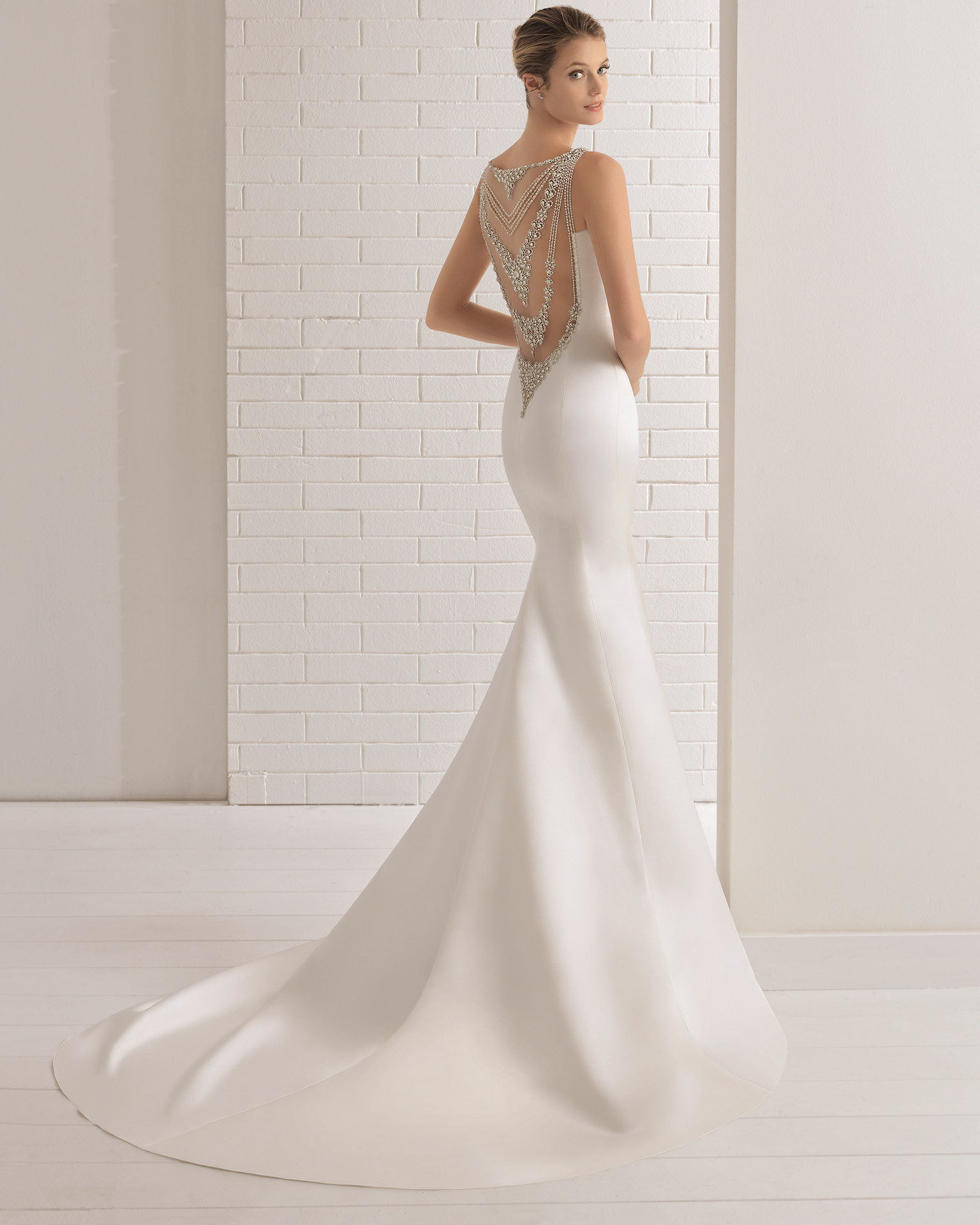 Mermaid-style duchess satin wedding dress with beaded V-neckline and jeweled back, in ivory.