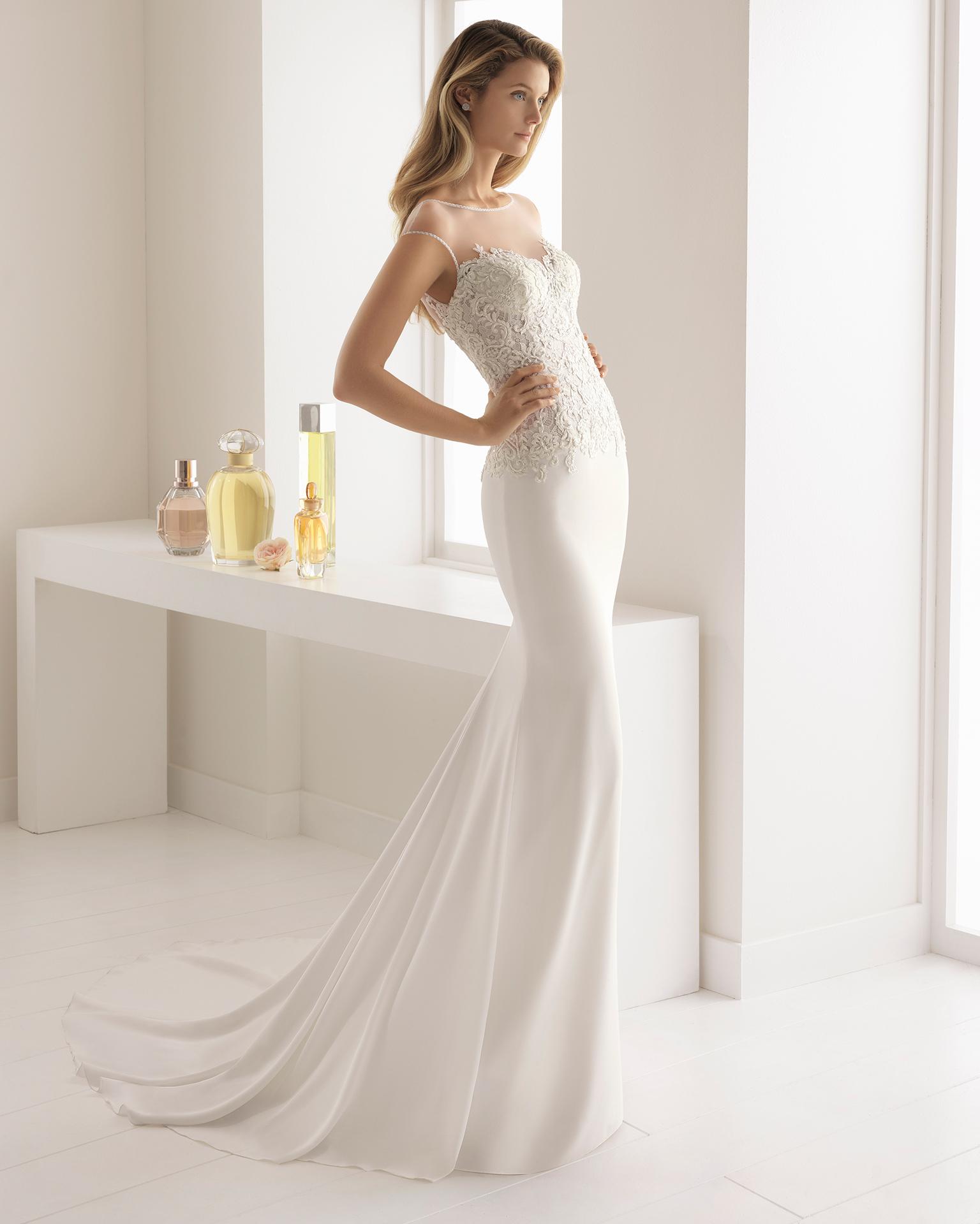 Abito da sposa taglio sirena in crêpe, pizzo trasparente e strass, con scollo illusione e schiena scollata.