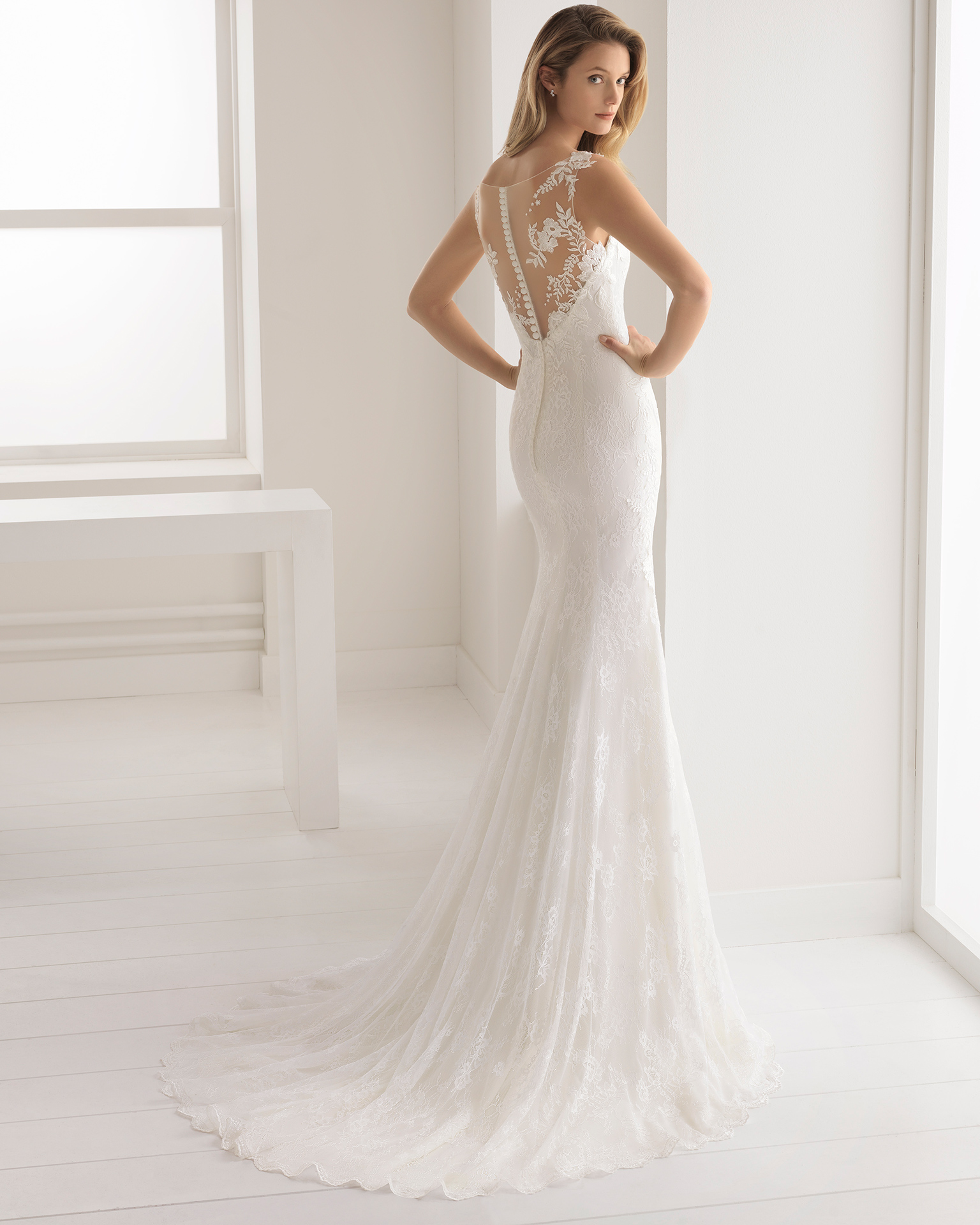 Mermaid-style beaded lace and crepe wedding dress with V-neckline and low back.