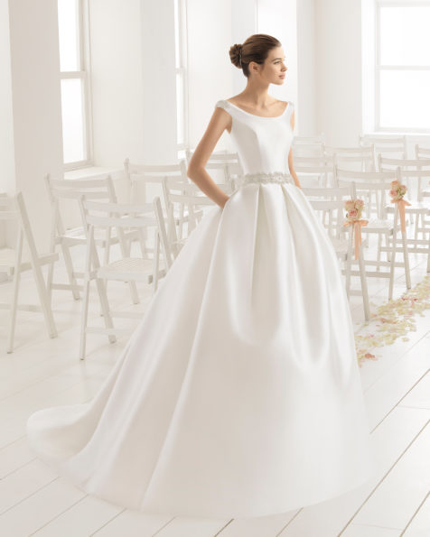 Classic-style tailored mikado wedding dress with bateau neckline, bow-tie back and beaded belt at waist, in natural.