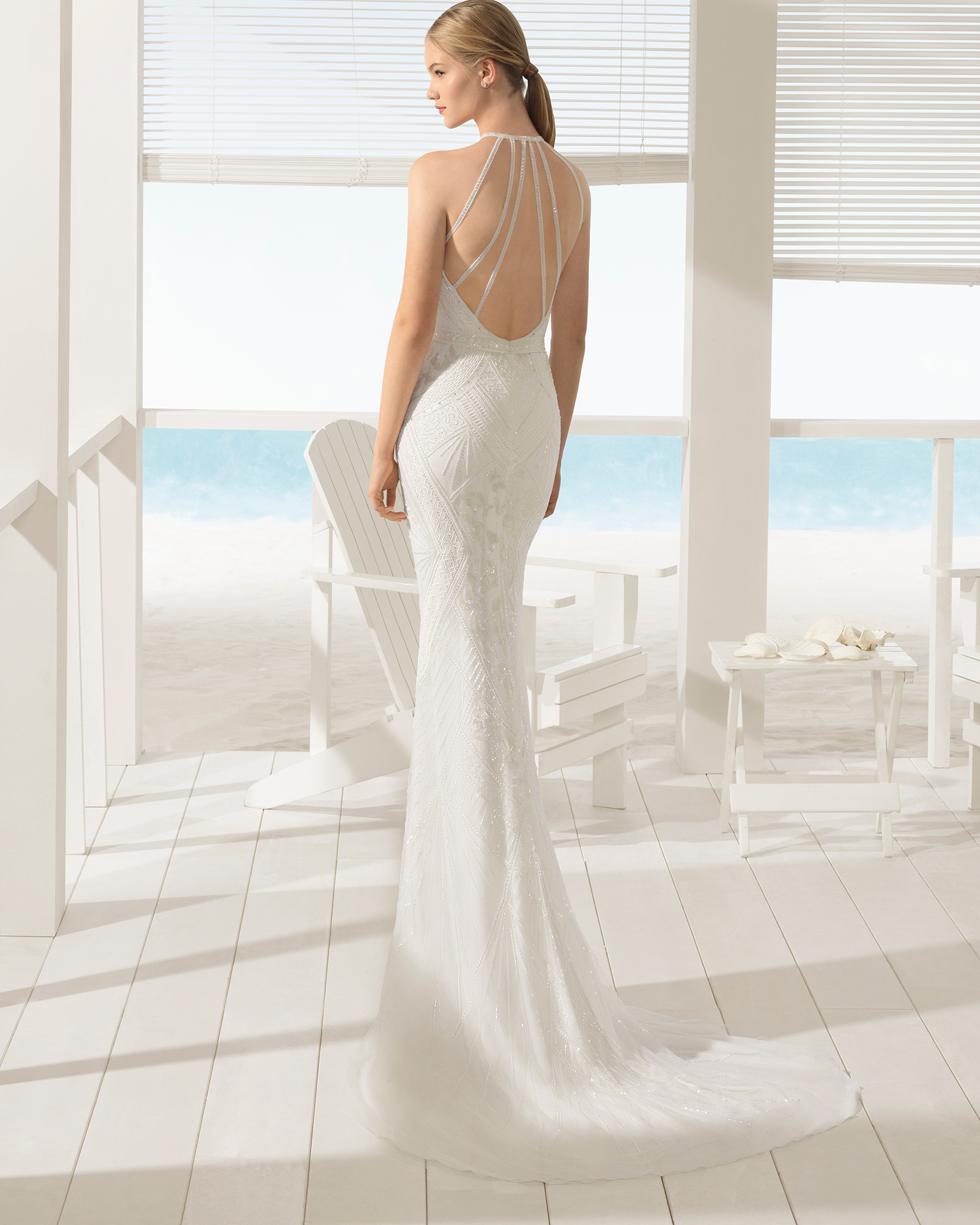 Boho-style beaded guipure lace wedding dress with halter neckline and open back.
