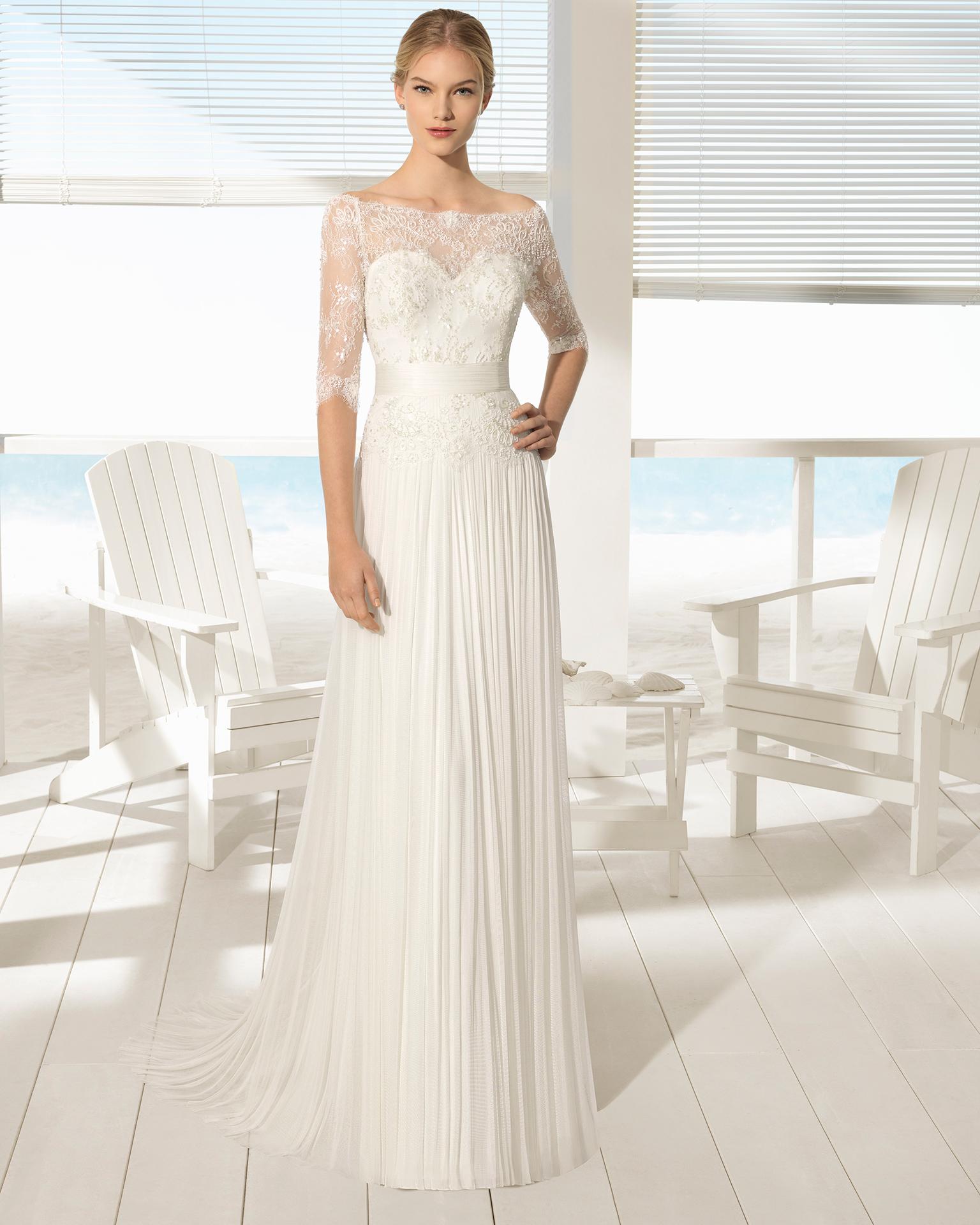 Robe de mariée style bohème en dentelle avec pierreries et mousseline de soie, manches longues et col illusion sur col en cœur.