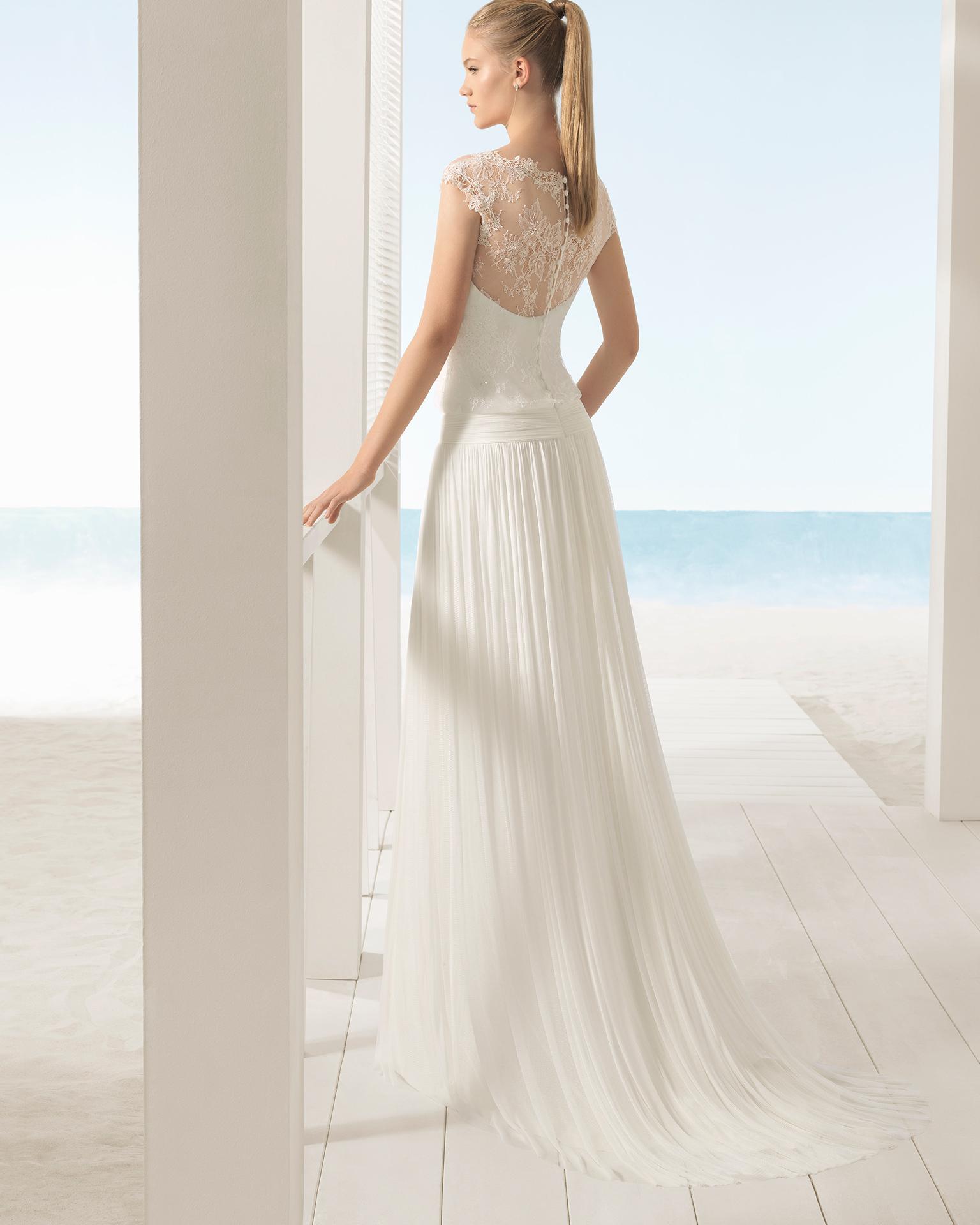 Vestido de novia estilo boho de encaje pedrería y muselina de seda, con escote ilusión sobre escote corazón y cuerpo ablusonado.