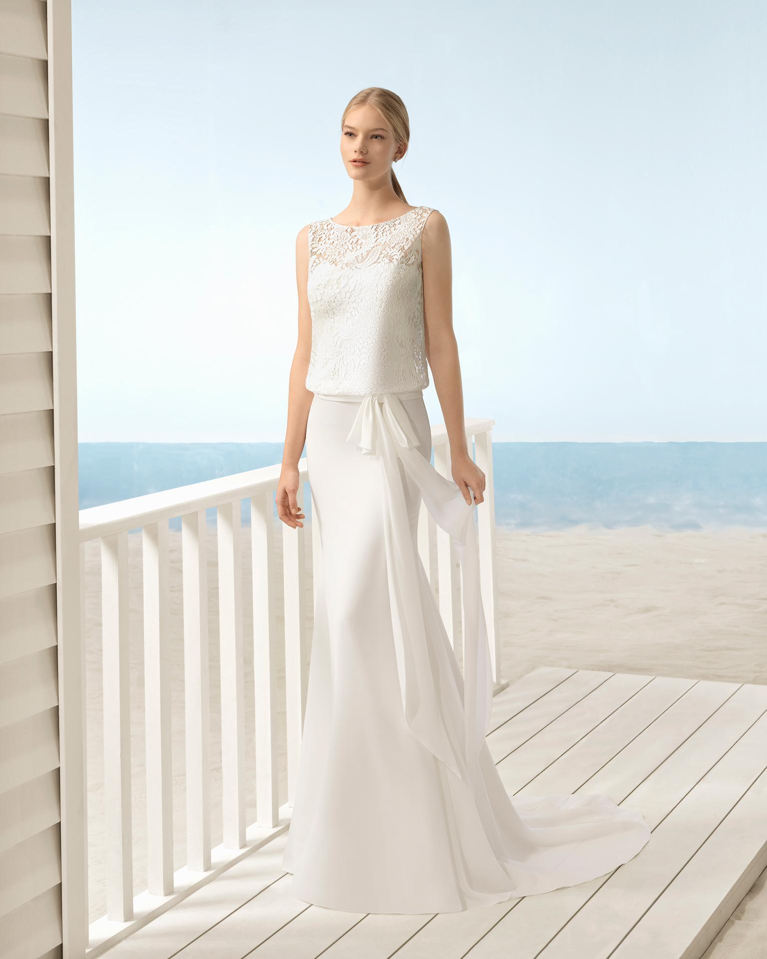 Robe de mariée style bohème en dentelle et gaze, avec col illusion sur un bustier et corsage blousant.
