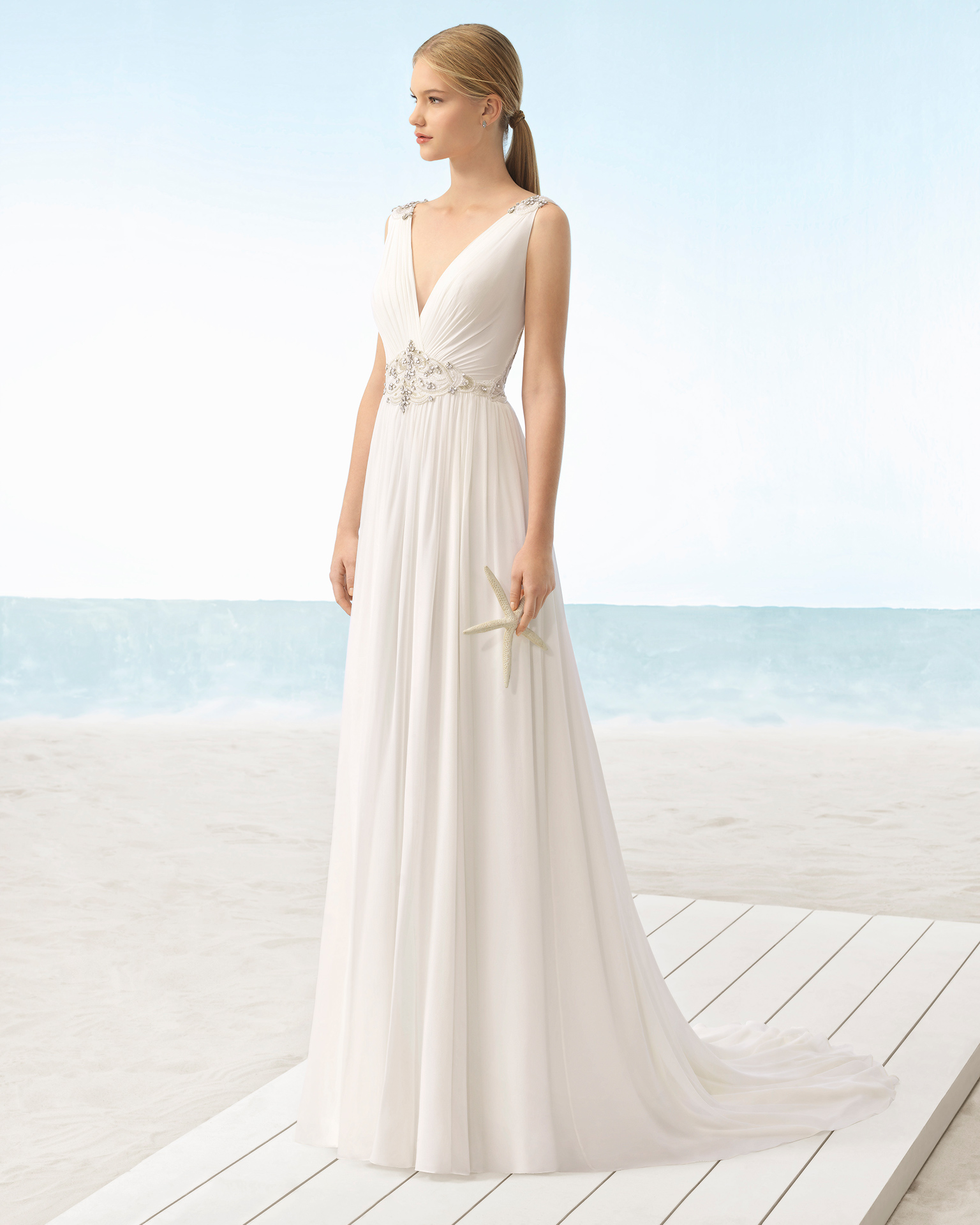 Boho-style silk chiffon wedding dress with V-neckline and jeweled back with beadwork detail.