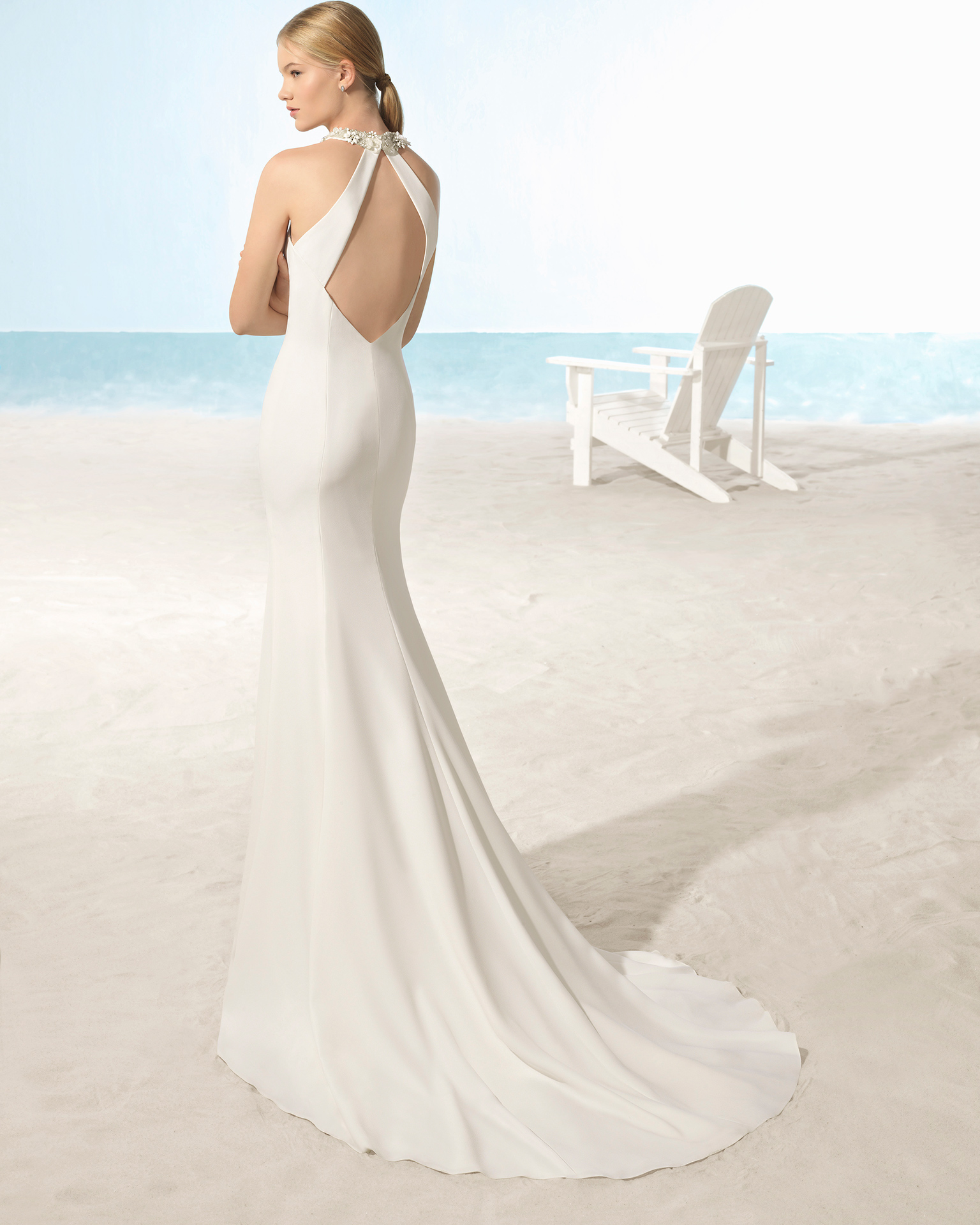 Mermaid-style crepe wedding dress with halter neckline, open back and crystal flowers.