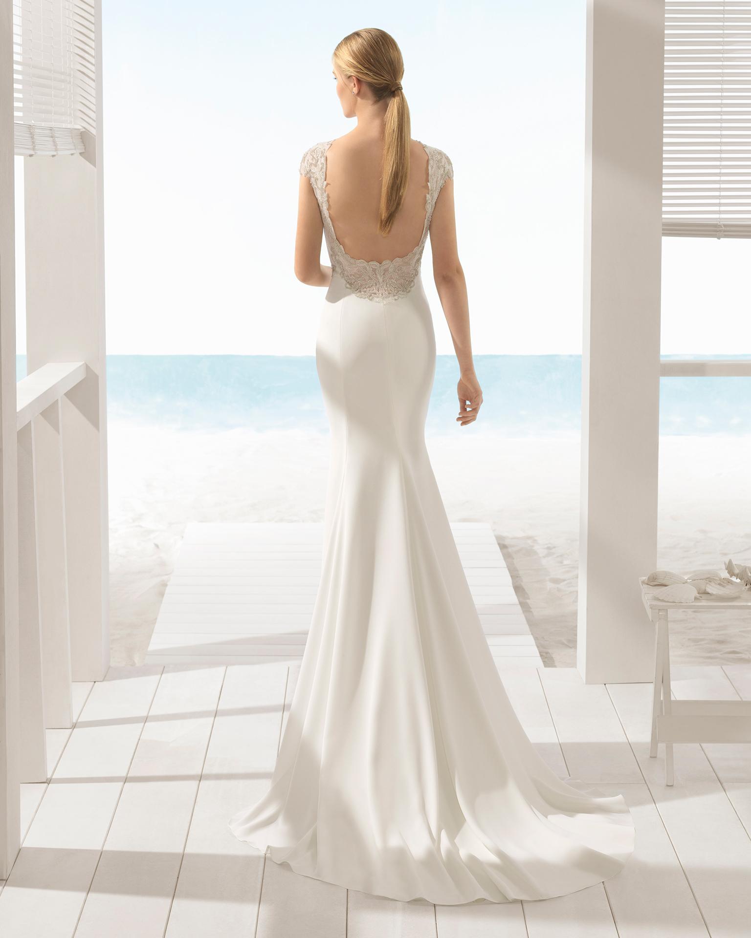 Rochie de mireasă în stil sirenă din crep și spatele decoltat, cu ornament din strasuri.