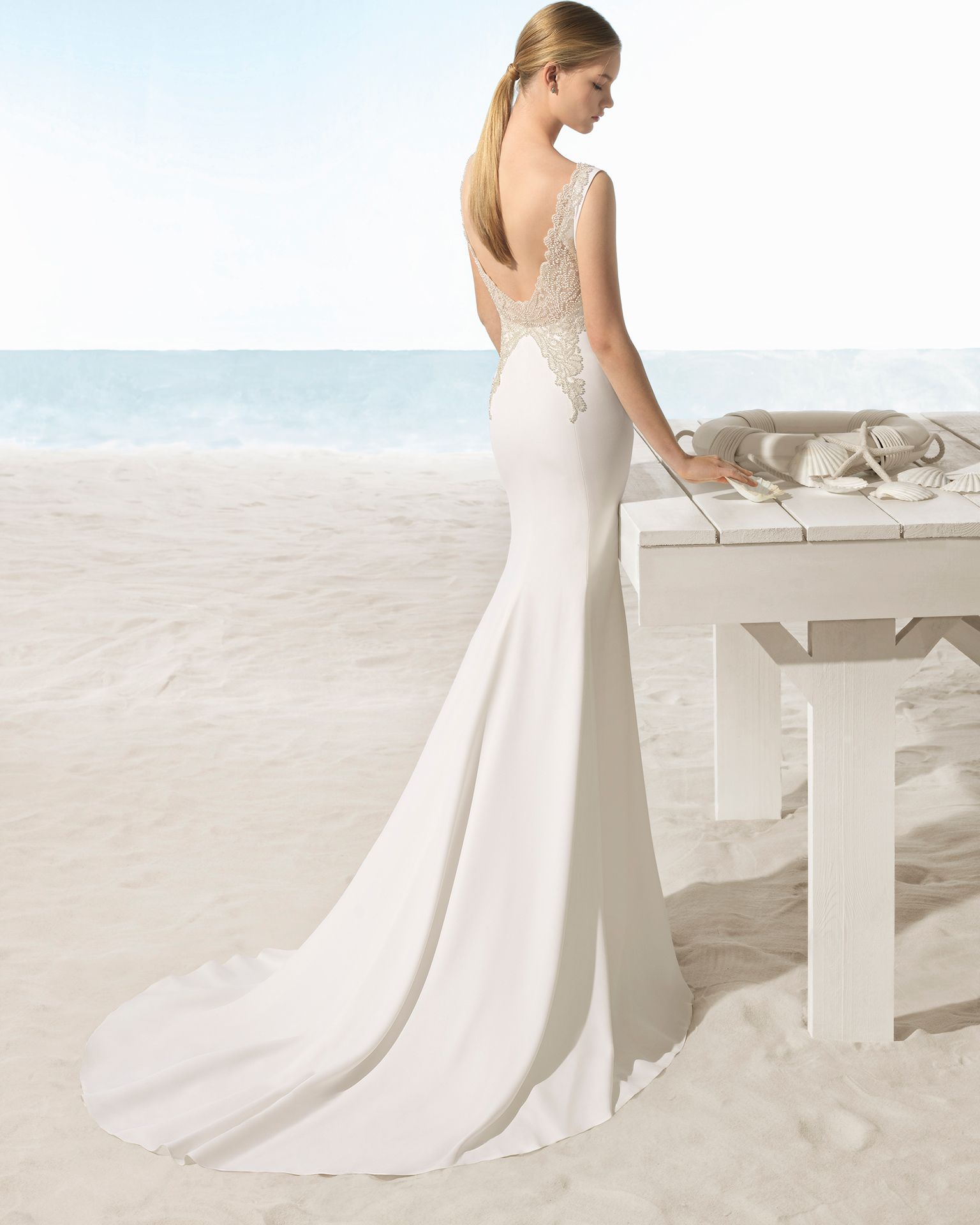 Mermaid-style crepe wedding dress with low back with beadwork detail.