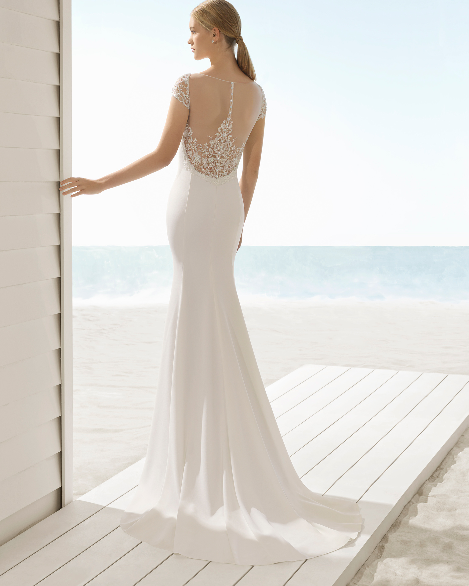 Mermaid-style crepe wedding dress with jeweled back.