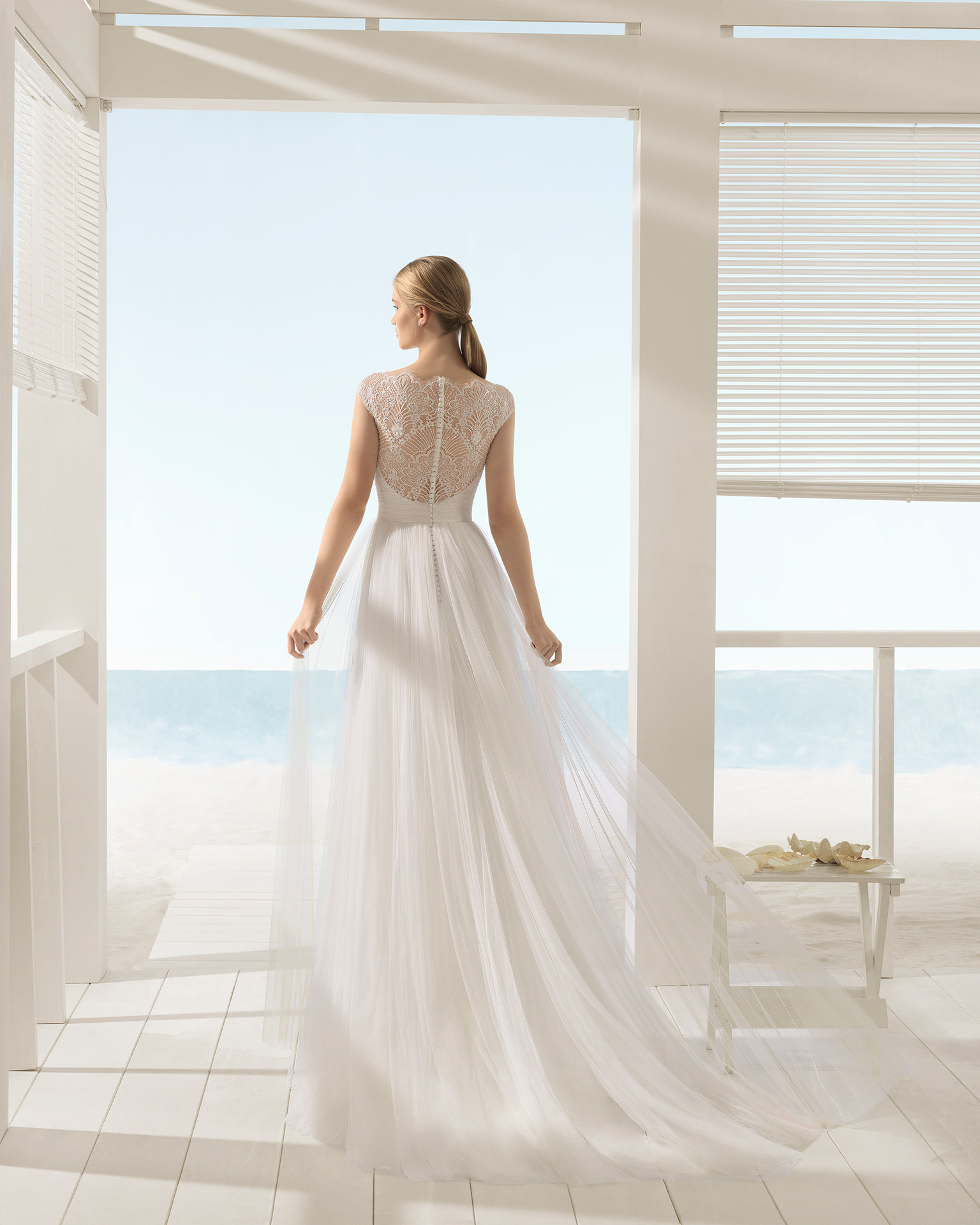 Rochie de mireasă în formă de A din tul și dantelă cu strasuri, cu mânecă scurtă cu spatele decoltat.