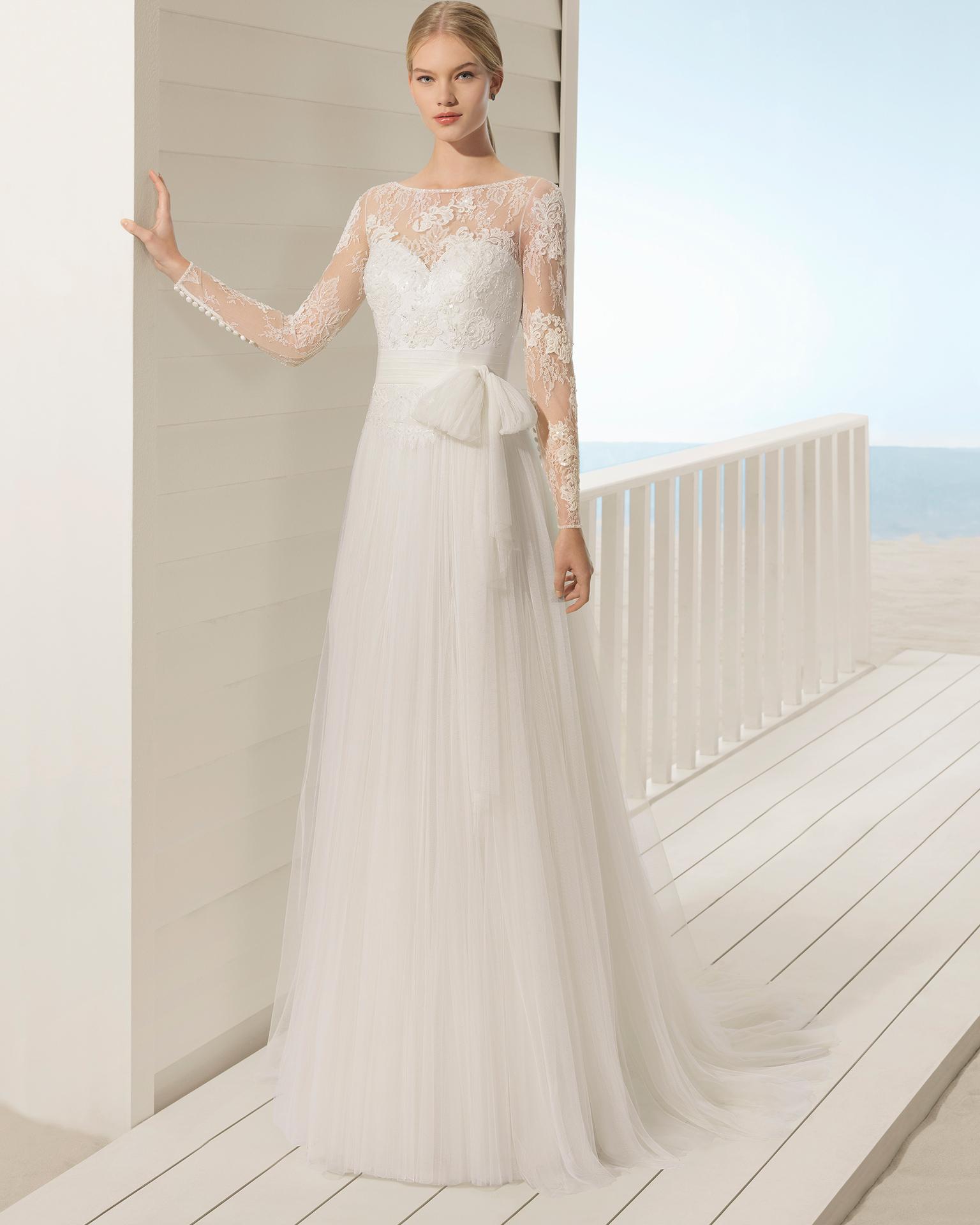 Robe de mariée style trapèze en tulle et dentelle avec pierreries à manches longues. Décolleté dans le dos avec transparences et jupe créant du volume.