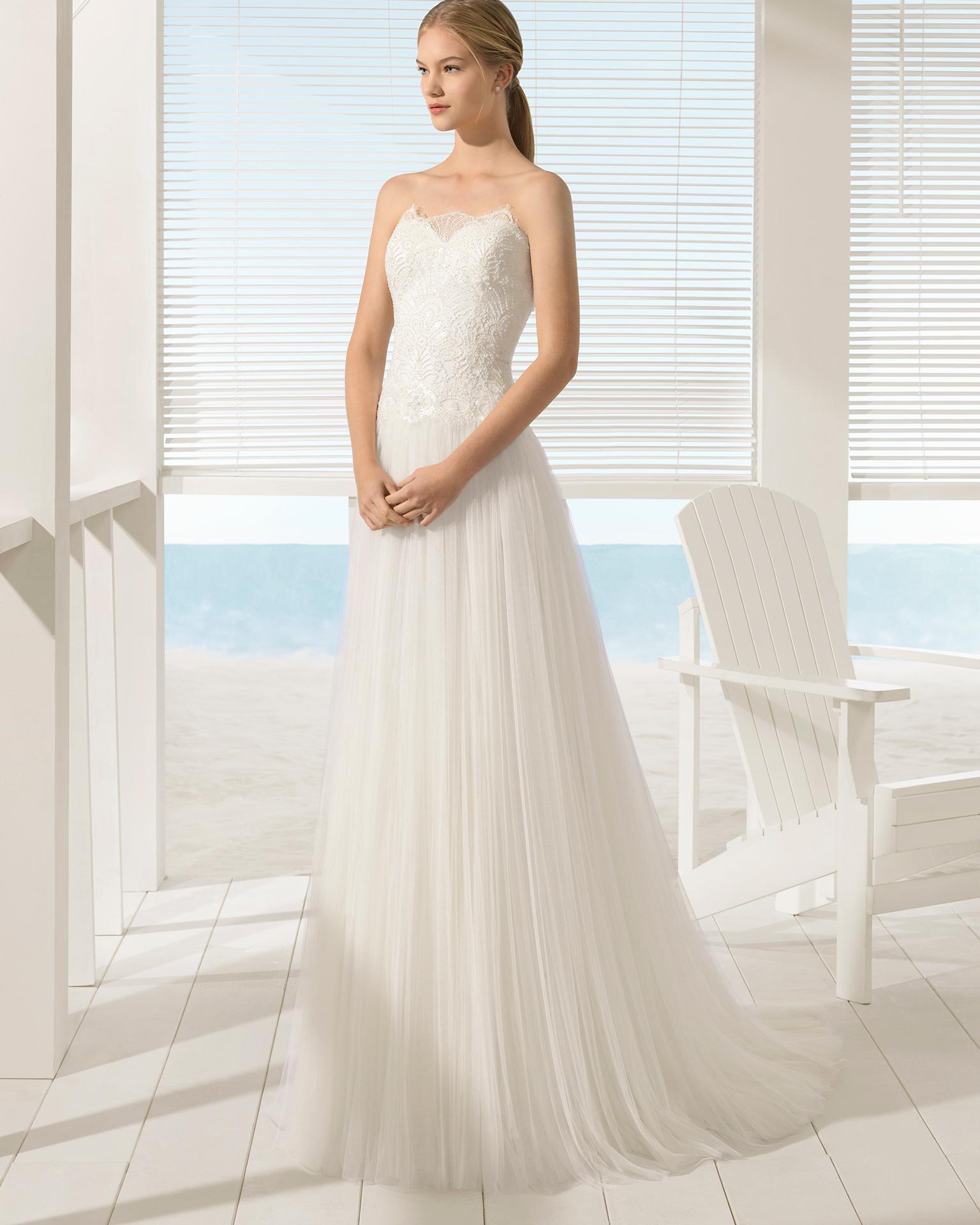 Robe de mariée style trapèze en tulle et dentelle avec pierreries, bustier avec transparences et veste.
