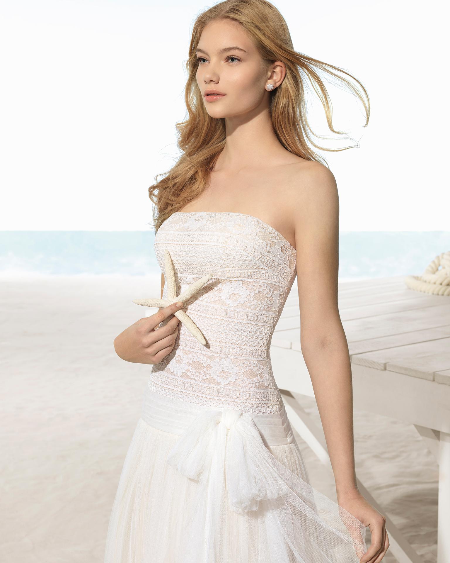 Robe de mariée style trapèze en tulle et dentelle, avec bustier, de couleur ivoire.