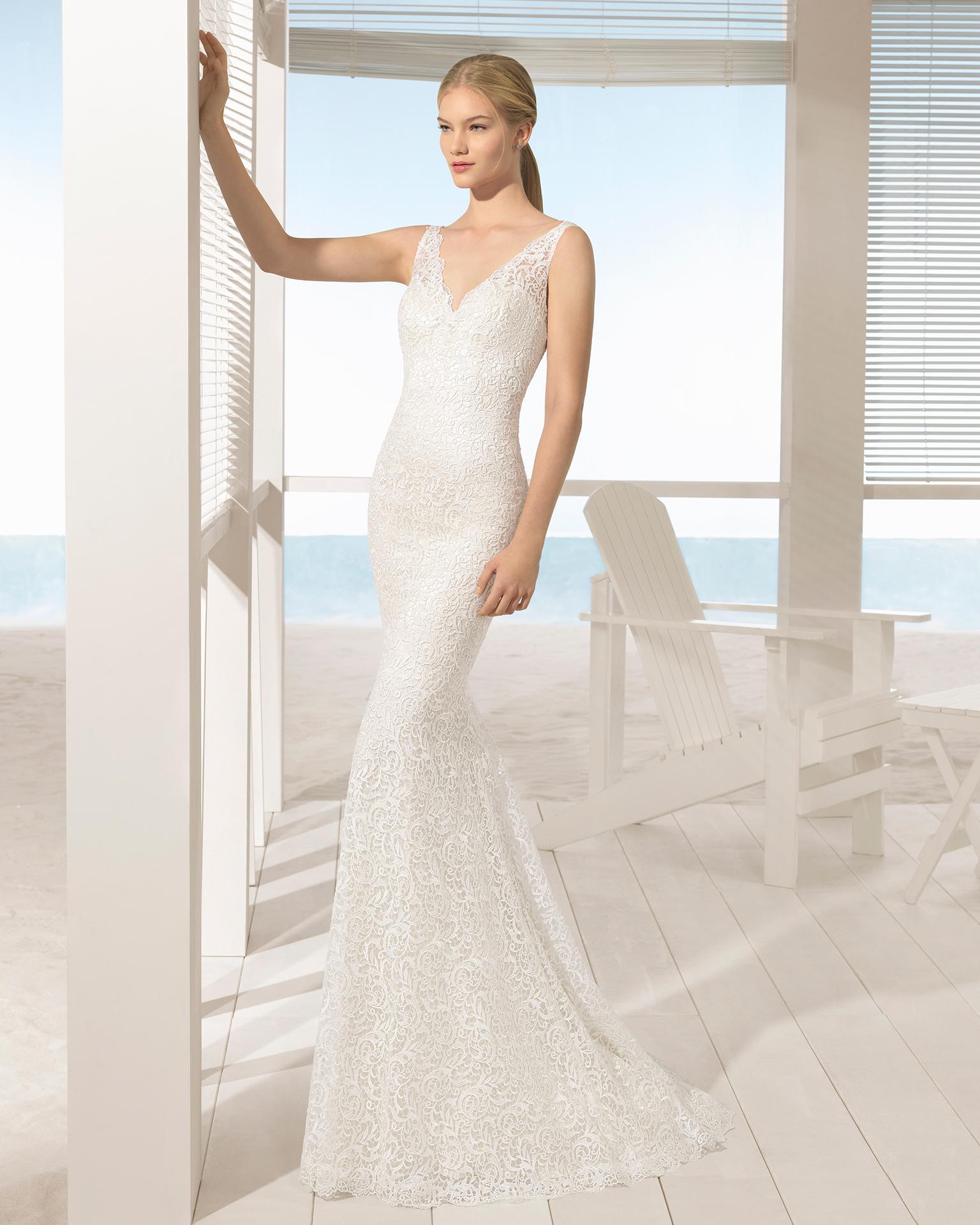 Robe de mariée style sirène en guipure avec décolleté dans le dos, de couleur ivoire.